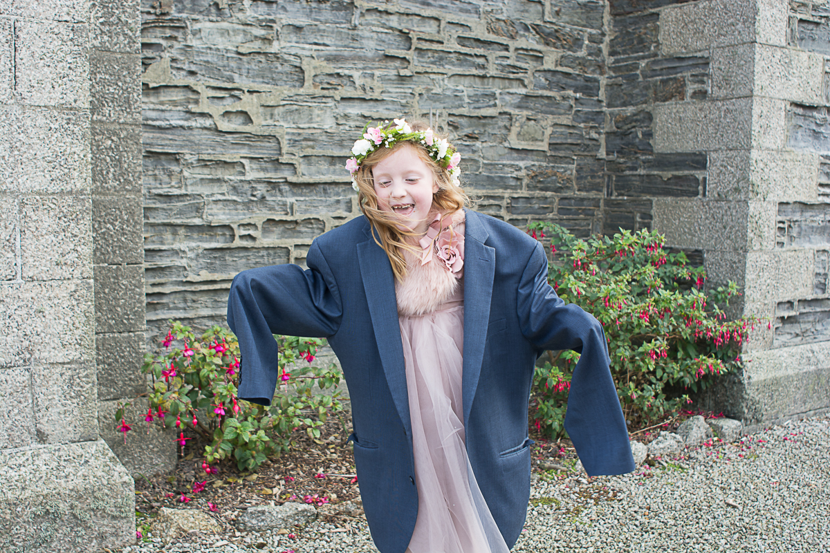adorable flowergirl with her dads jacket on in porthleven