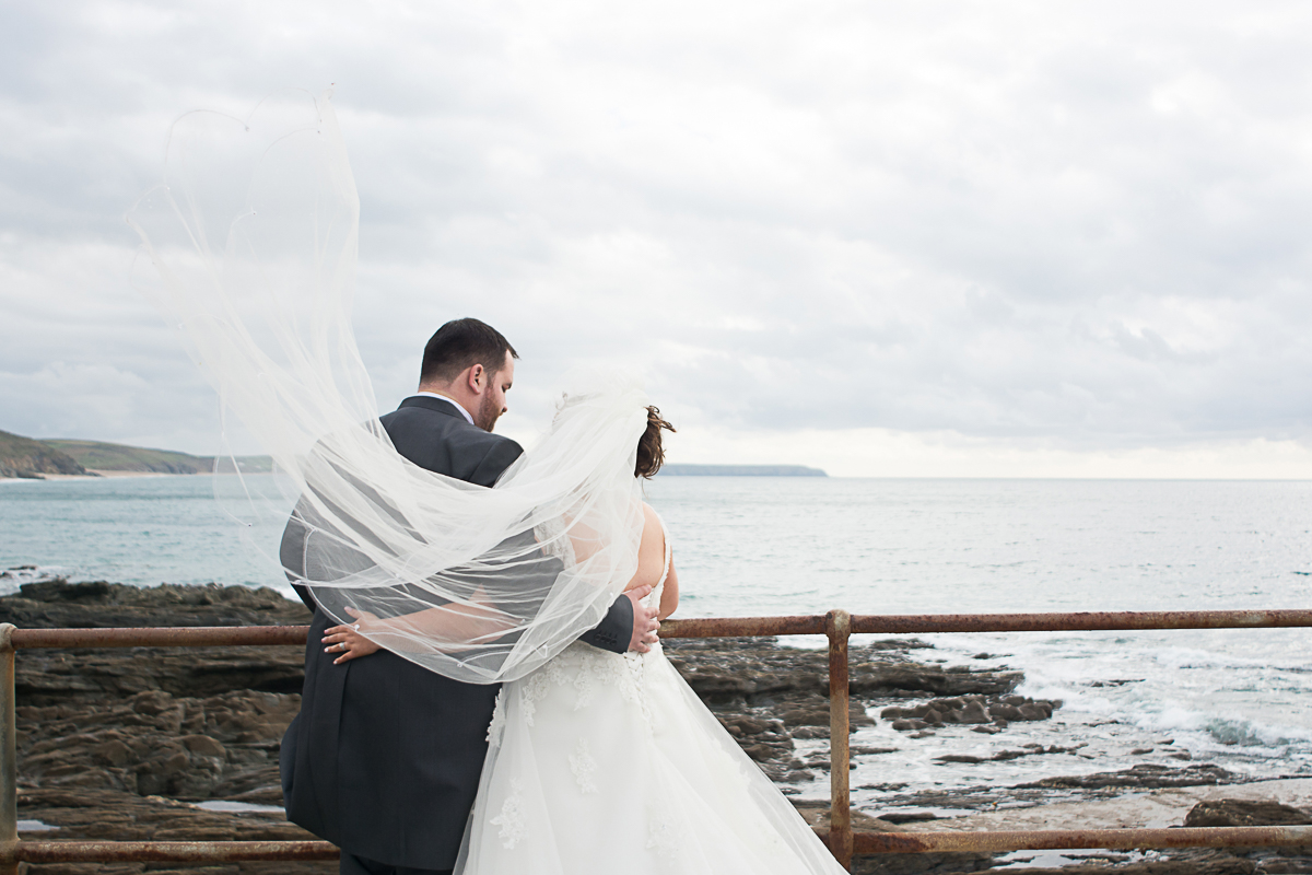 bride and groom look out to sea in porthleven