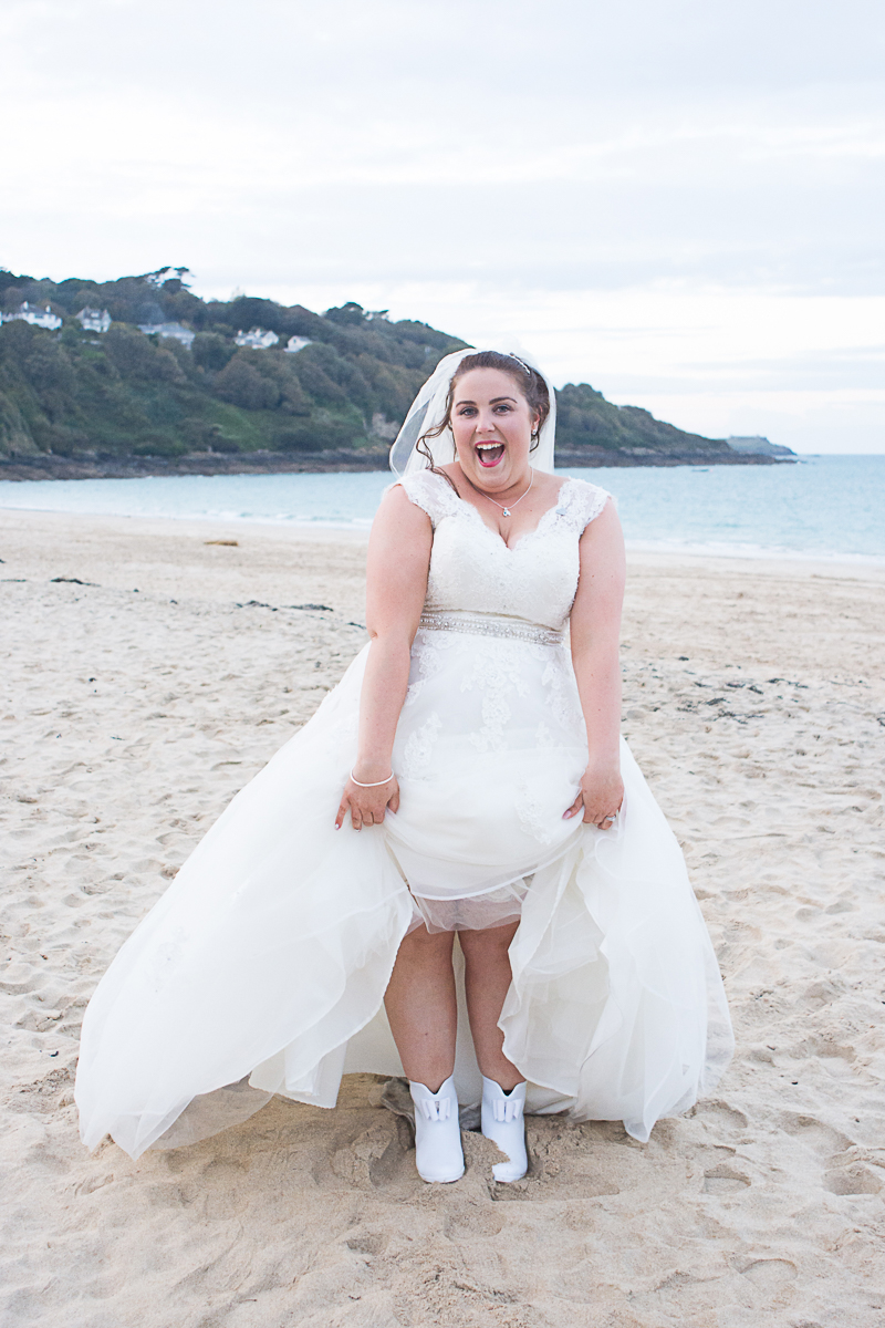 bride with wellies on the beach at carbis bay cornwall