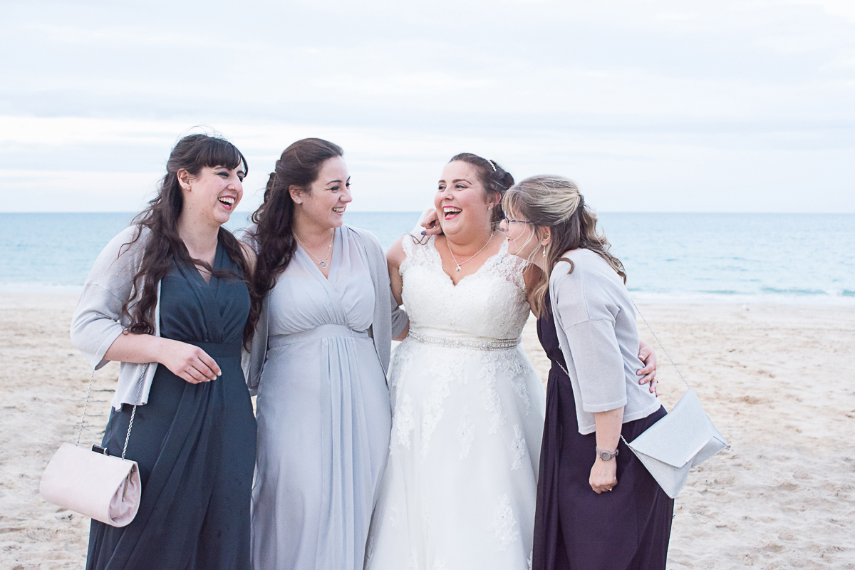 bride and bridesmaids laughing on carbis bay beach cornwall