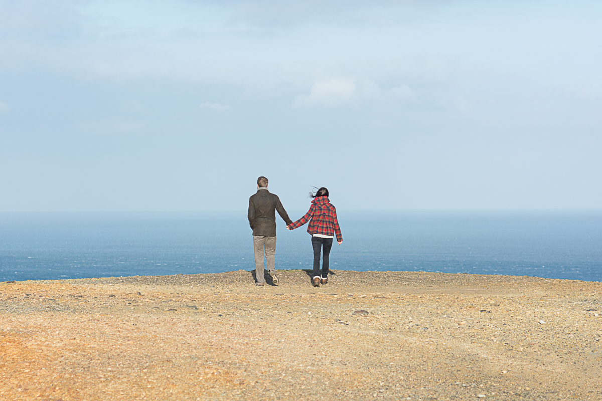 engaged couple hold hands and look at the sea in St Agnes Cornwall