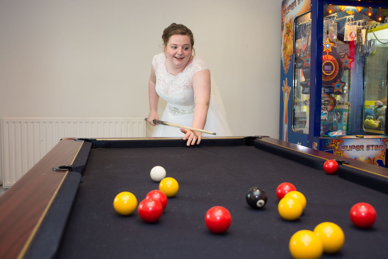 playing pool in her wedding dress at waterside cornwall