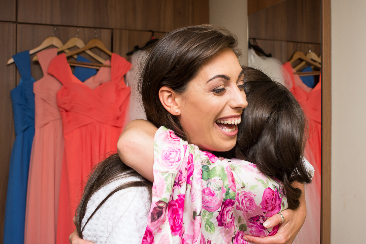 Bride and her sister have a big hug with the dresses in the background at Boringdon Hall