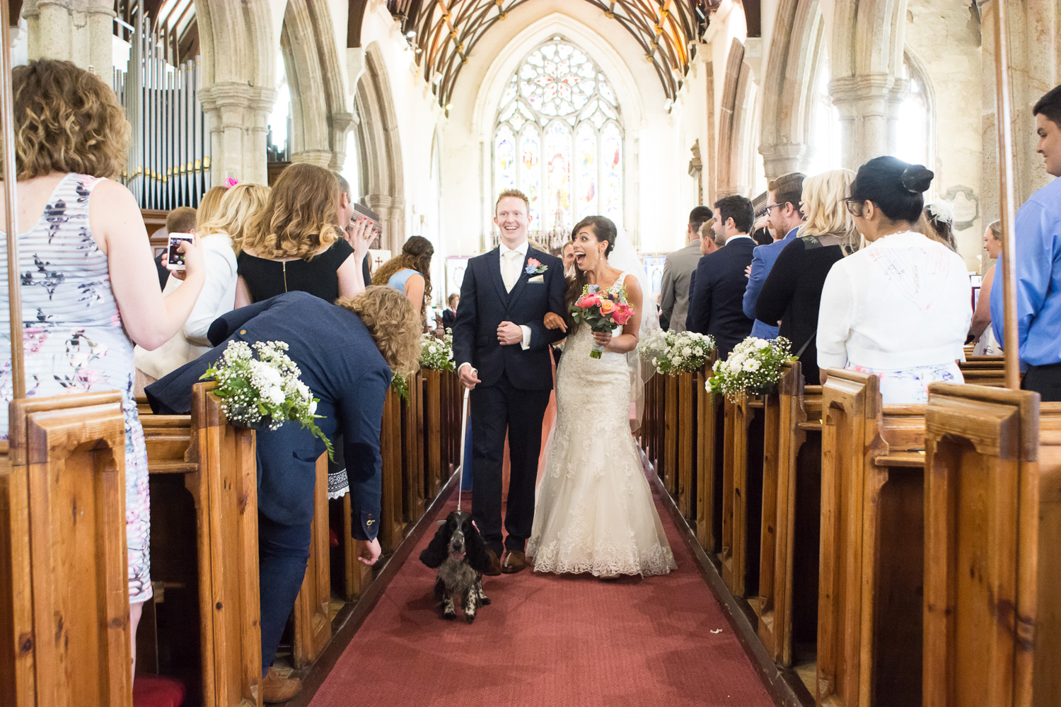 the bride, groom and their dog walk down the aisle at st mary's church plympton plymouth