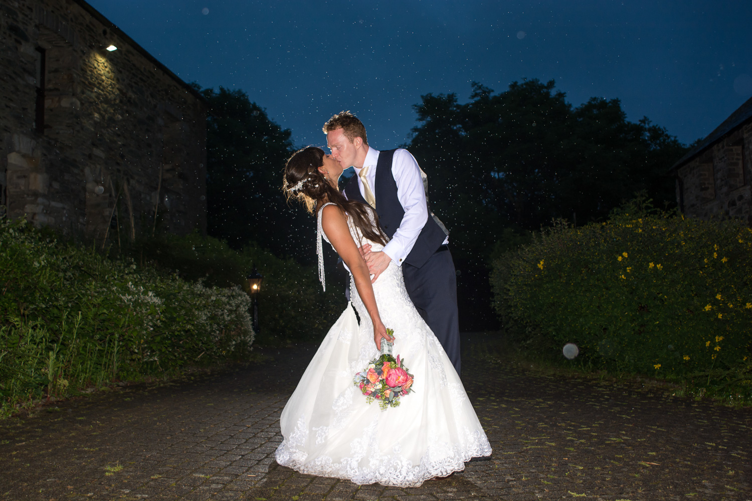 Bride and Groom kissing in the rain at their Boringdon Hall Plymouth wedding