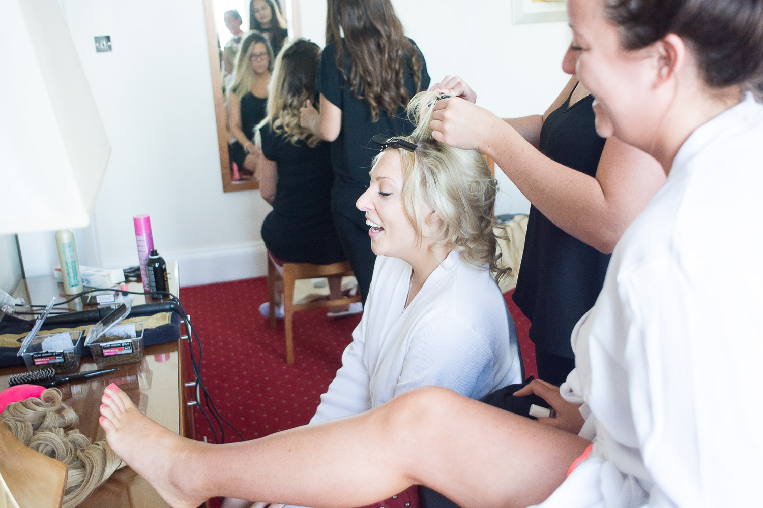 bridesmaid shows the bride her painted toenails at the Headland Hotel Torquay