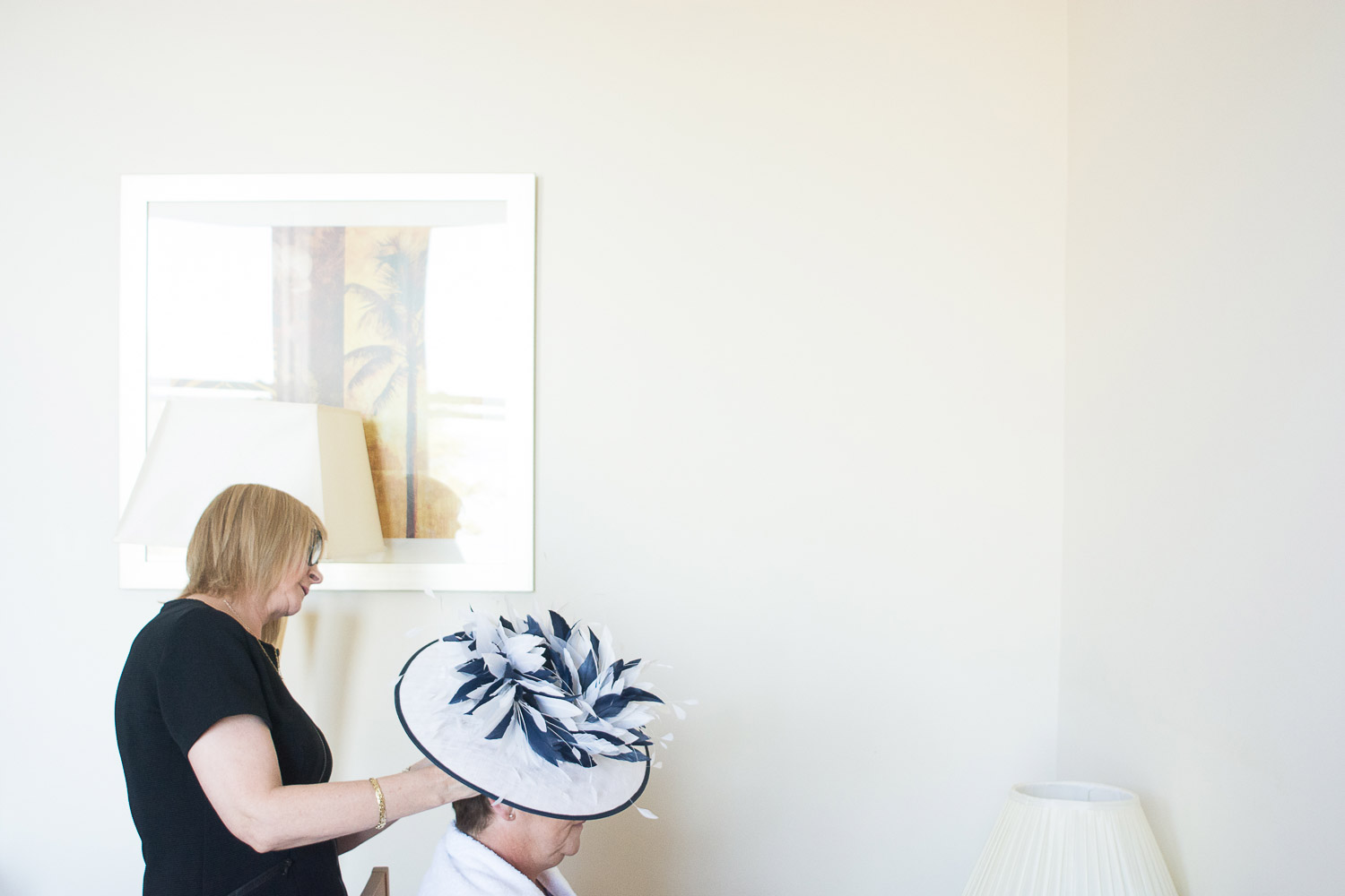 Mother of the bride puts her wedding hat on