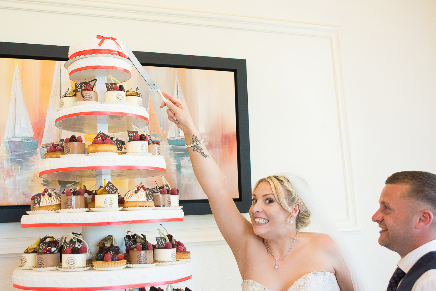 the bride and groom cut the super tall cake at the Headland Hotel Torquay