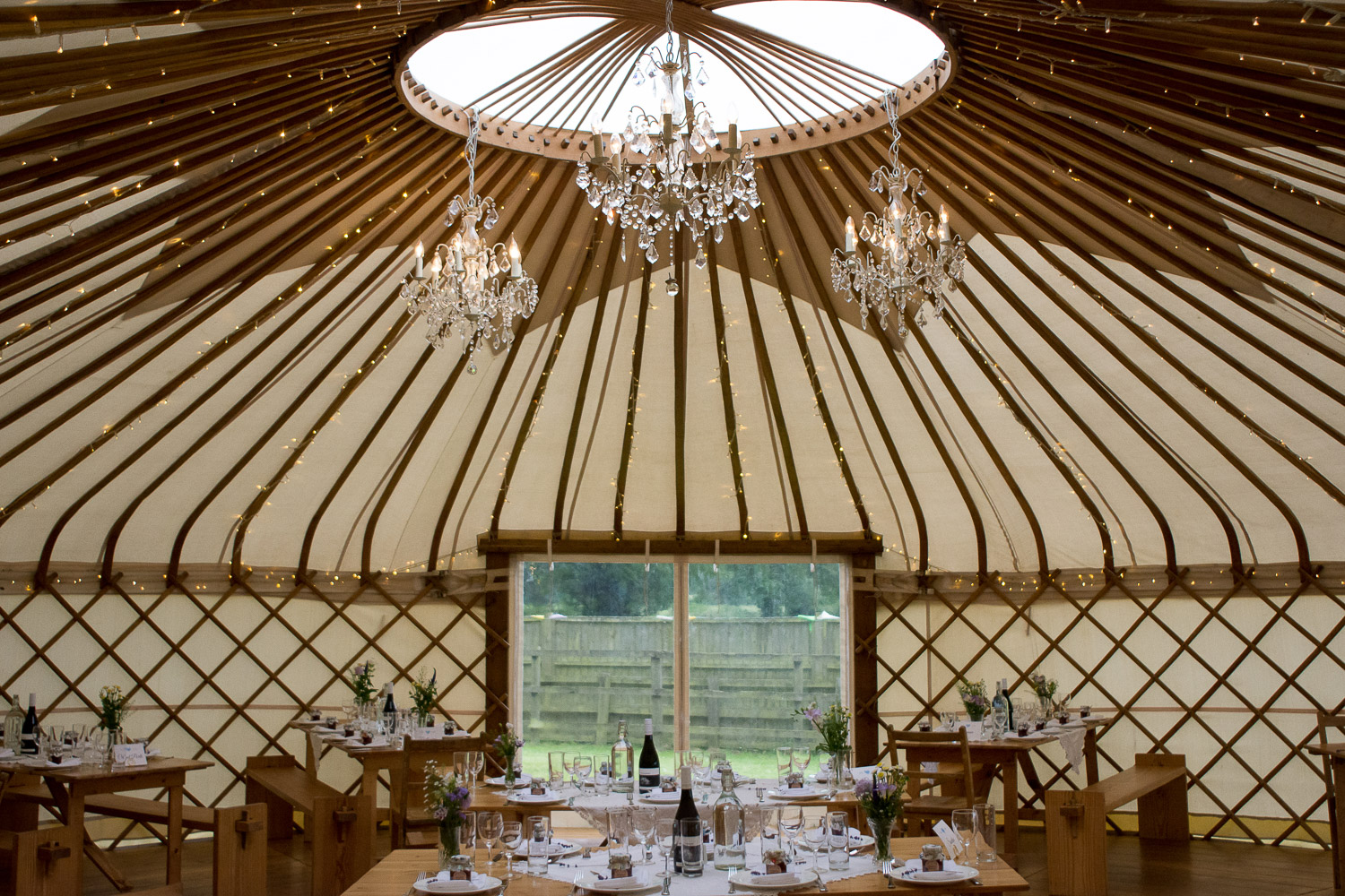 inside of the wedding yurt lit with fairy lights at wedding yurts wedding in leicestershire