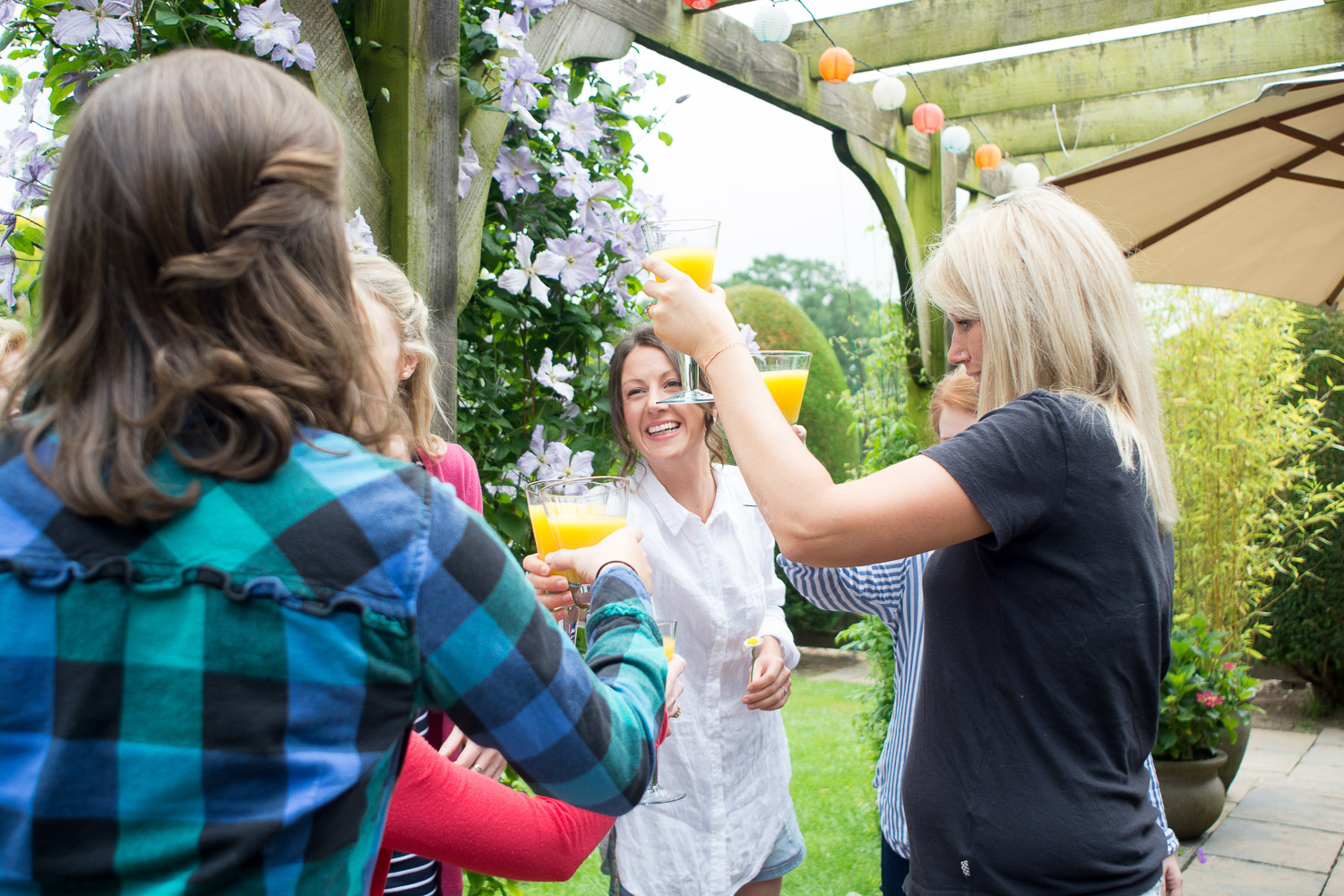 bride and the girls raise a glass of bucks fizz in the garden at wedding yurts wedding in leicestershire