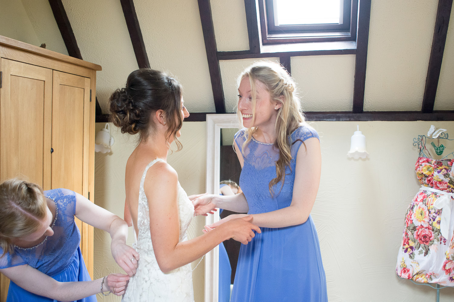 bride being helped into her dress and excitedly smiling with her sister at wedding yurts wedding in leicestershire