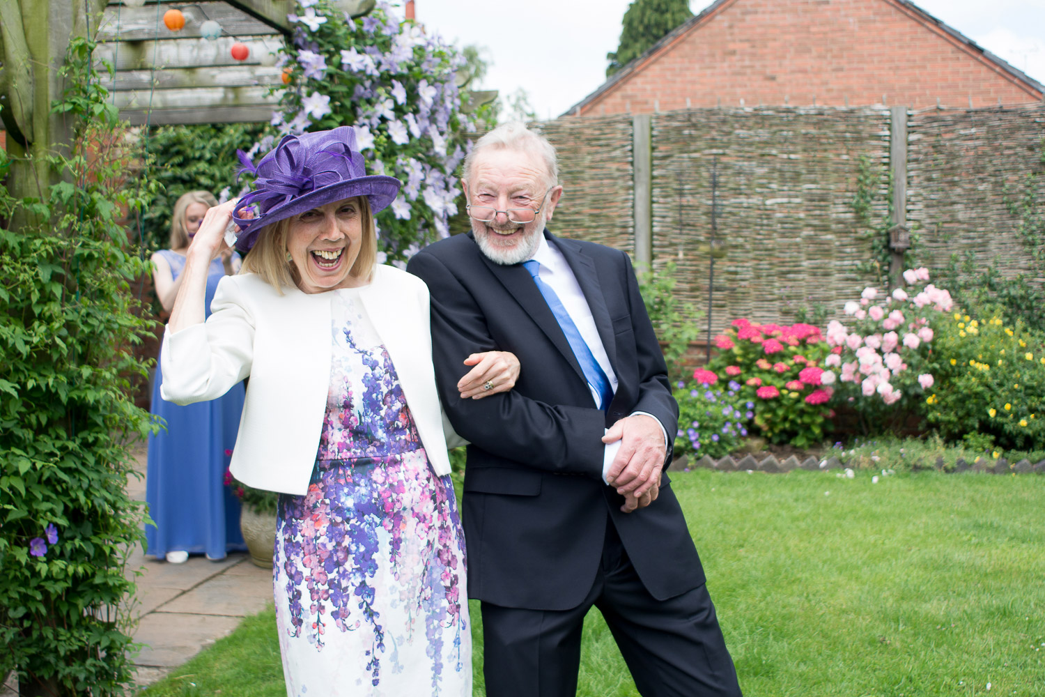 brides parents arm in arm with huge smiles at wedding yurts wedding in leicestershire