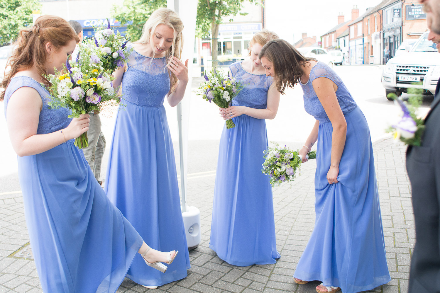bridesmaids looking at their shoes outside lutterworth town hall