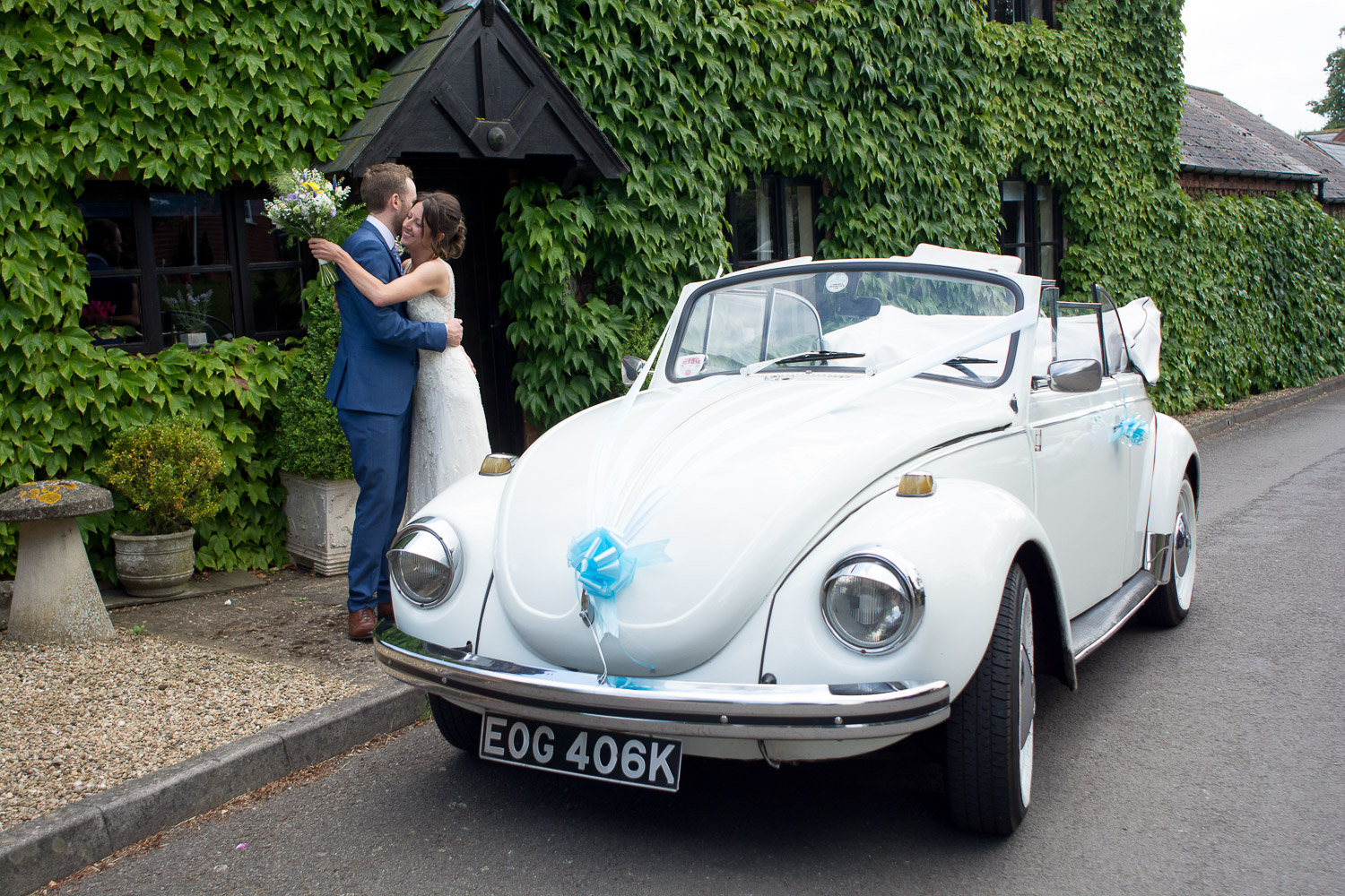 bride and groom cuddle next to their convertible vw beetle at wedding yurts wedding in leicestershire
