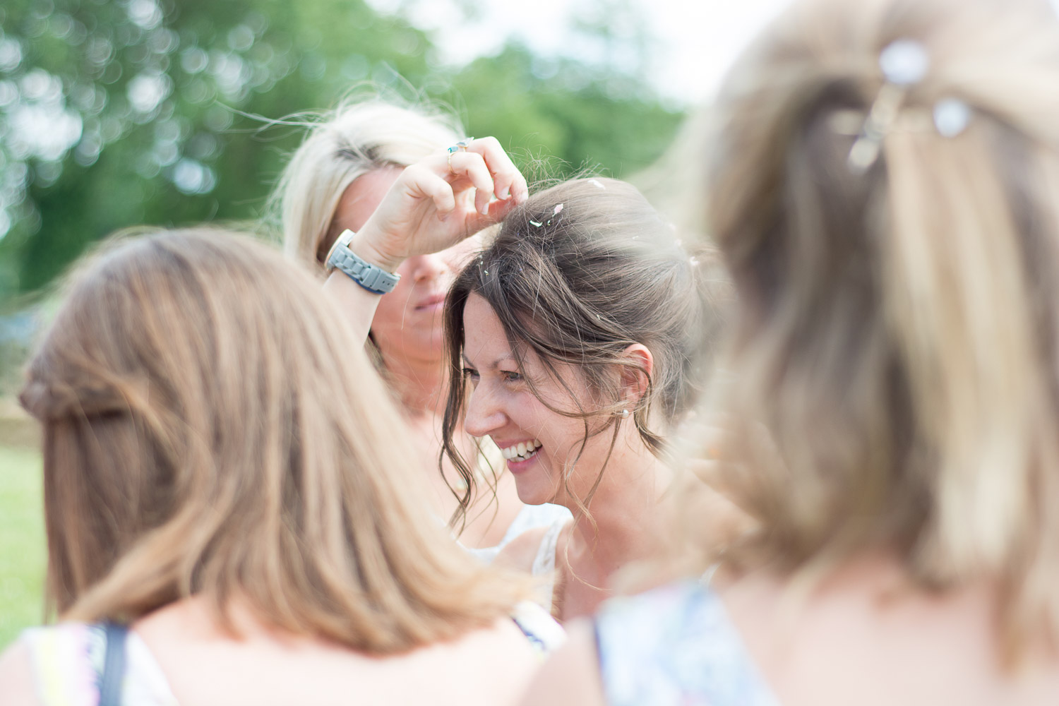 picking confetti out of her hair at wedding yurts wedding in leicestershire