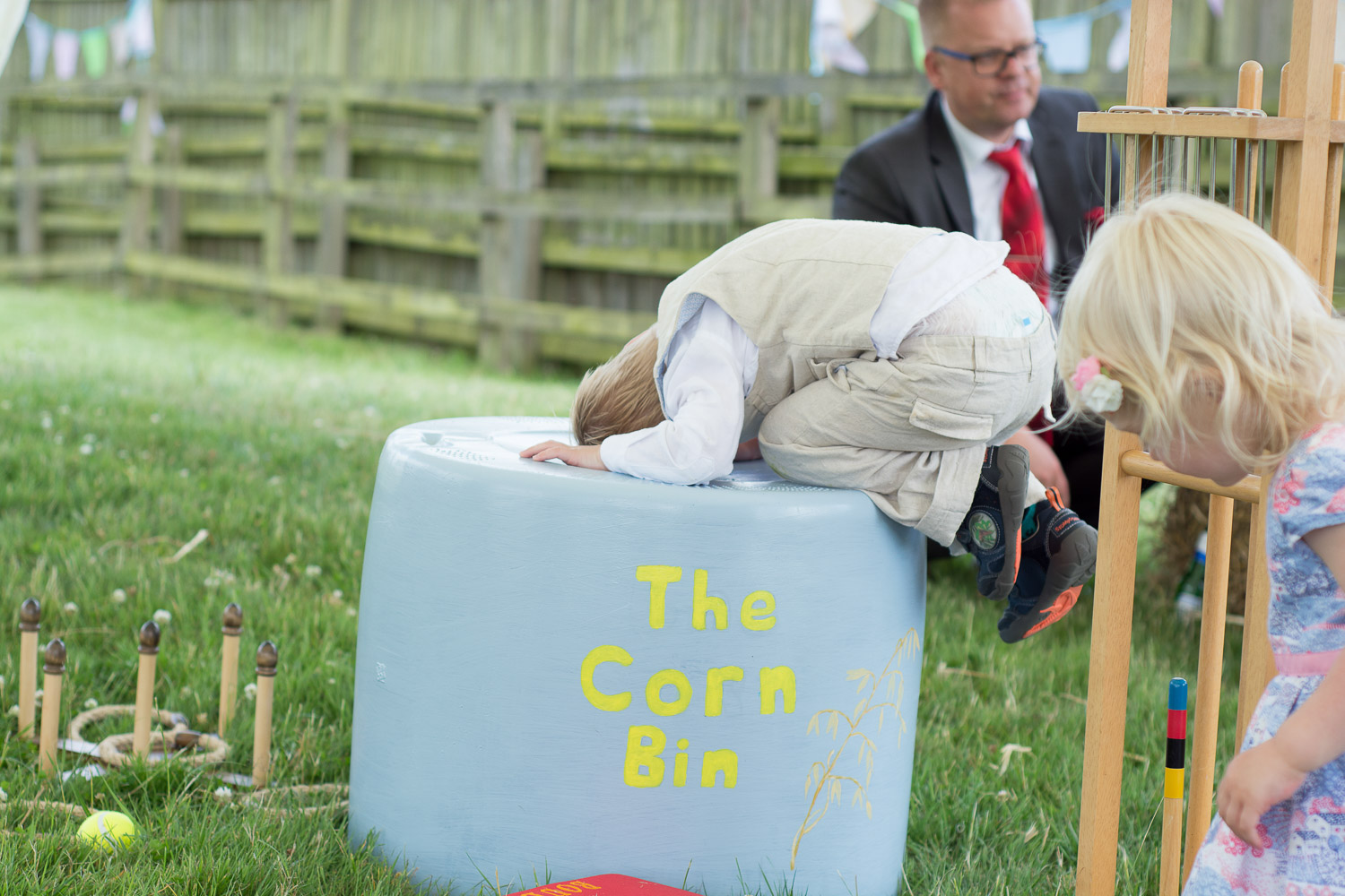 boy with is head in the corn bin at wedding yurts wedding in leicestershire