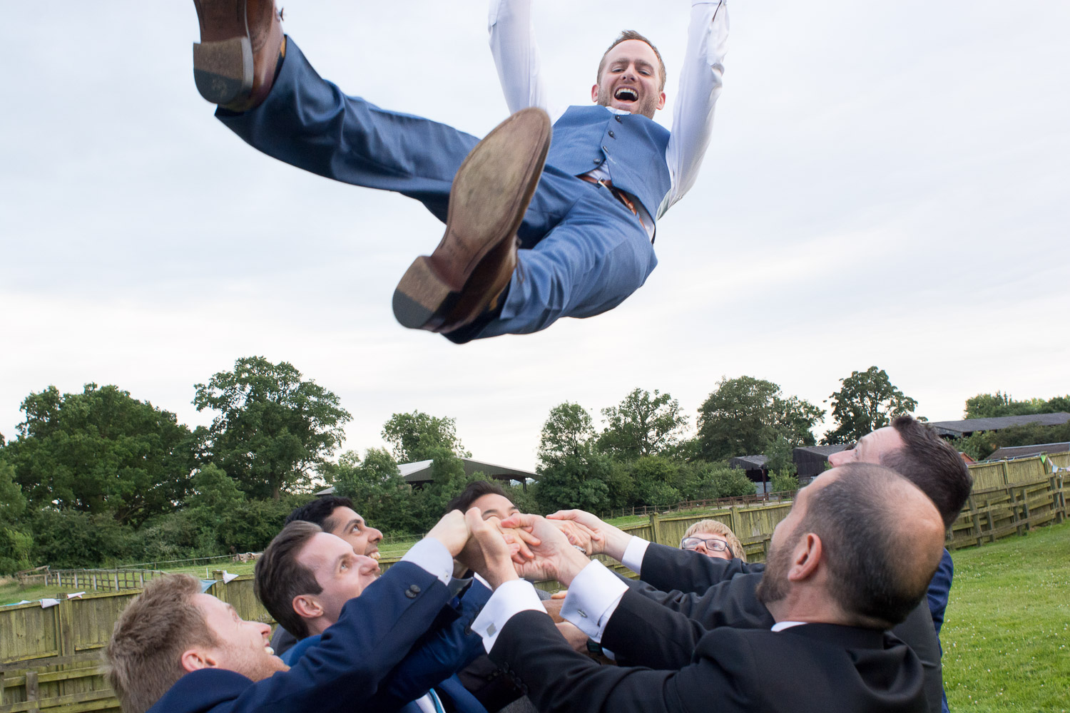 men throw the groom high in the air at wedding yurts wedding in leicestershire
