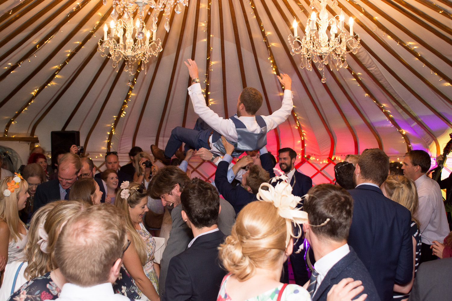 groom crowd surfing at wedding yurts wedding in leicestershire