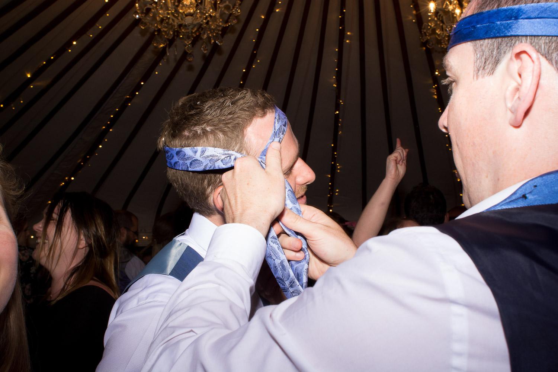 groom has his tie on his head on the dancefloor at wedding yurts wedding in leicestershire