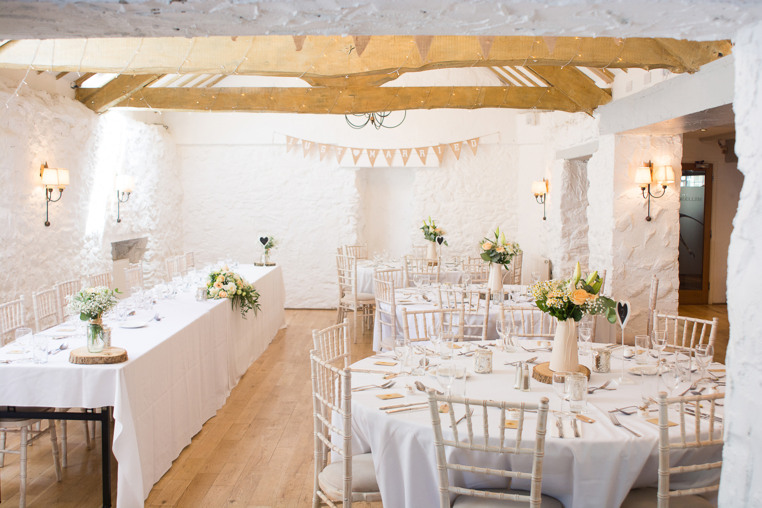 Exposed beams and tables set for the wedding breakfast at the wonderful Bickley Mill Wedding Venue in Devon