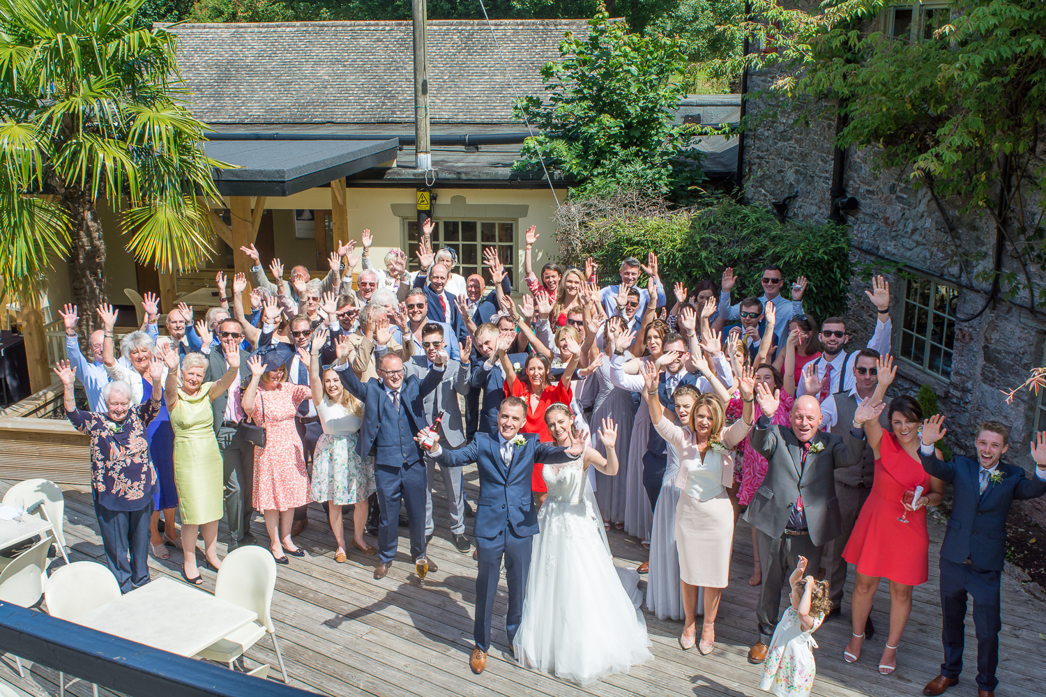 Big group photo from above on the decking at the Bickley Mill wedding venue in Devon