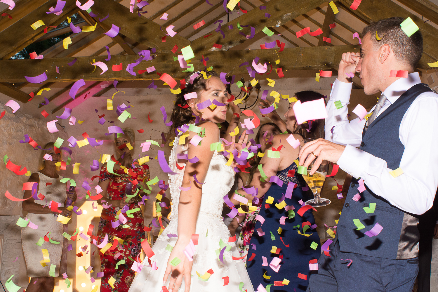 Confetti covers the bride and groom on the dance floor at the Bickley Mill wedding venue in Devon
