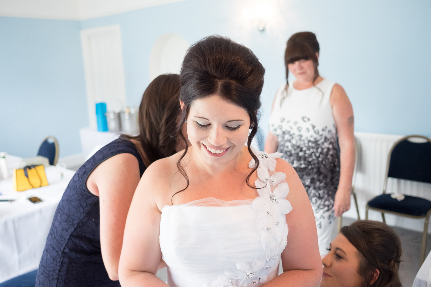 bride being helped into her dress and smiling the whole time at The Lord Haldon Hotel in Devon