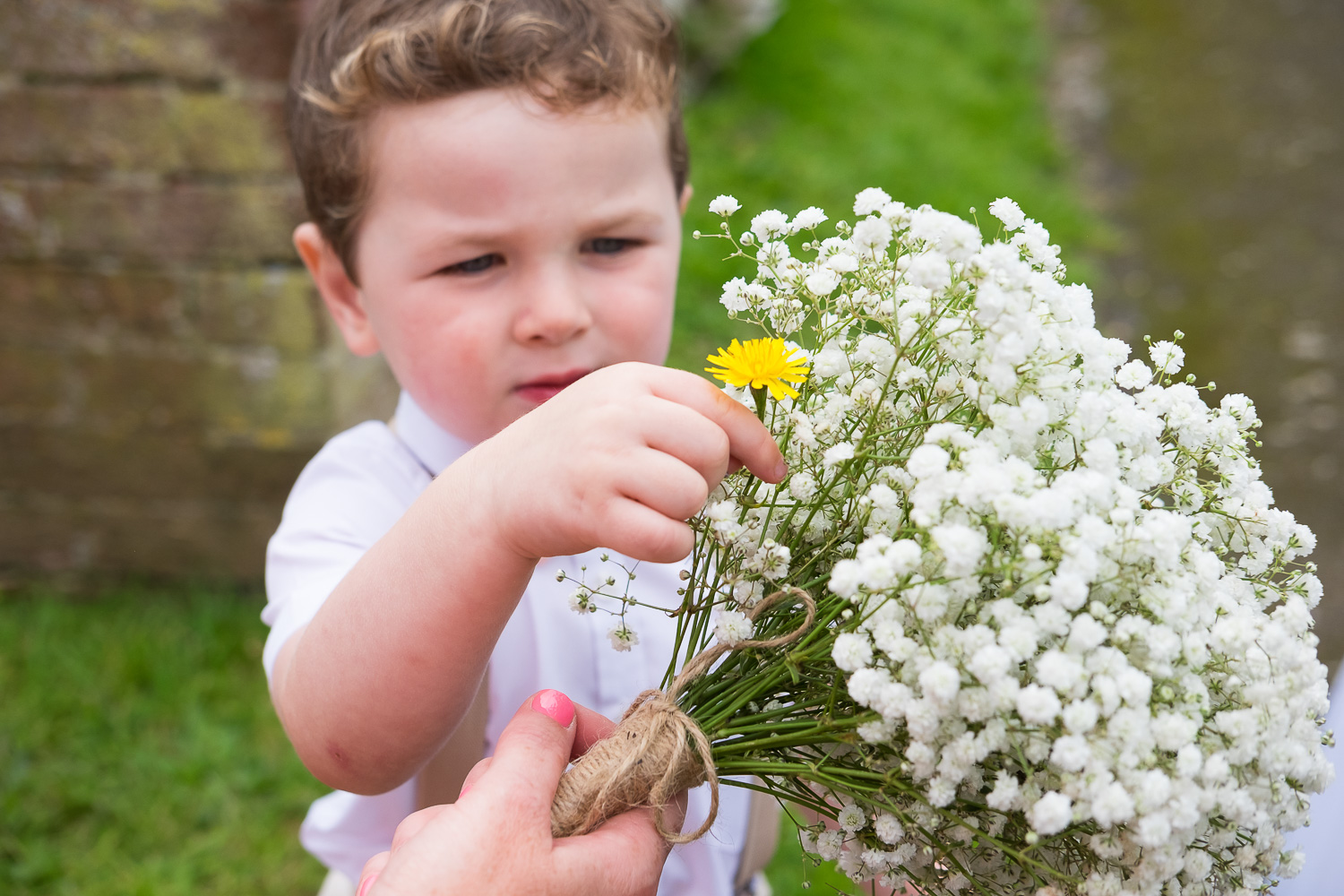 page boy picks a yellow flower for his mum and puts it into her bouquet outside st mary's church in woolacombe