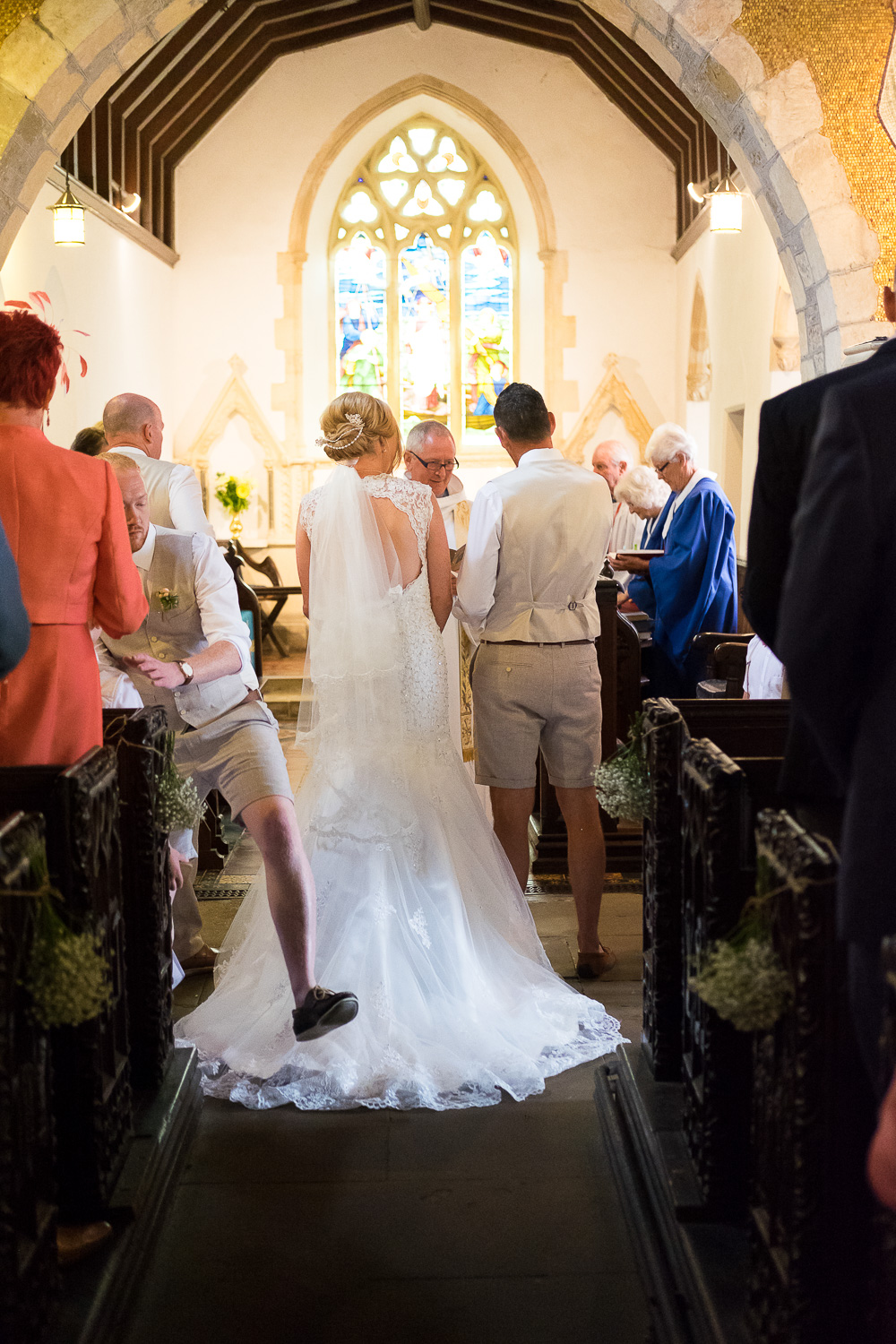 big step over the brides dress during the ceremony at st mary's church in woolacombe