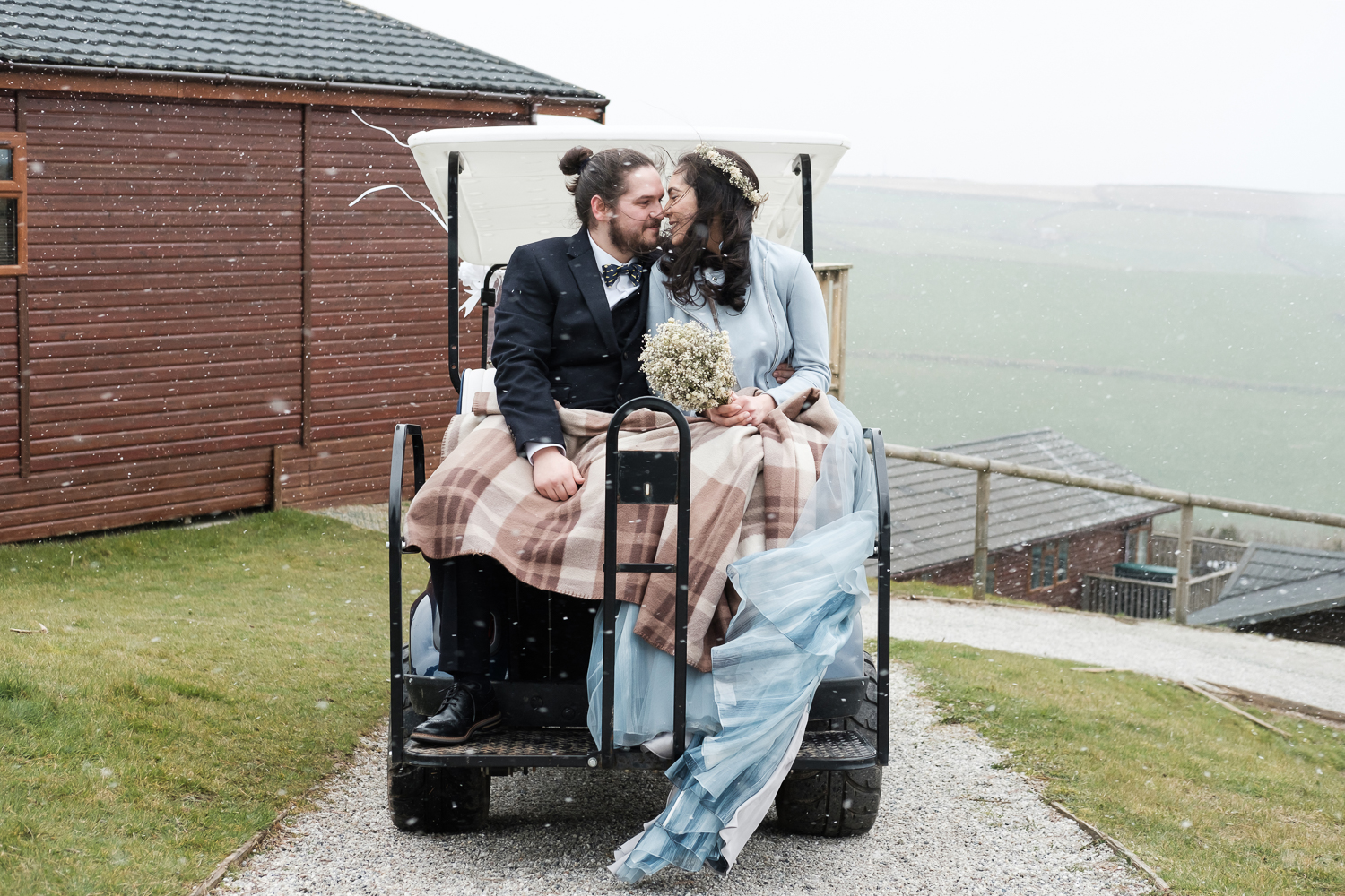 Married couple about to kiss in a golf cart in the snow at their Whitsand Bay Fort wedding in Cornwall