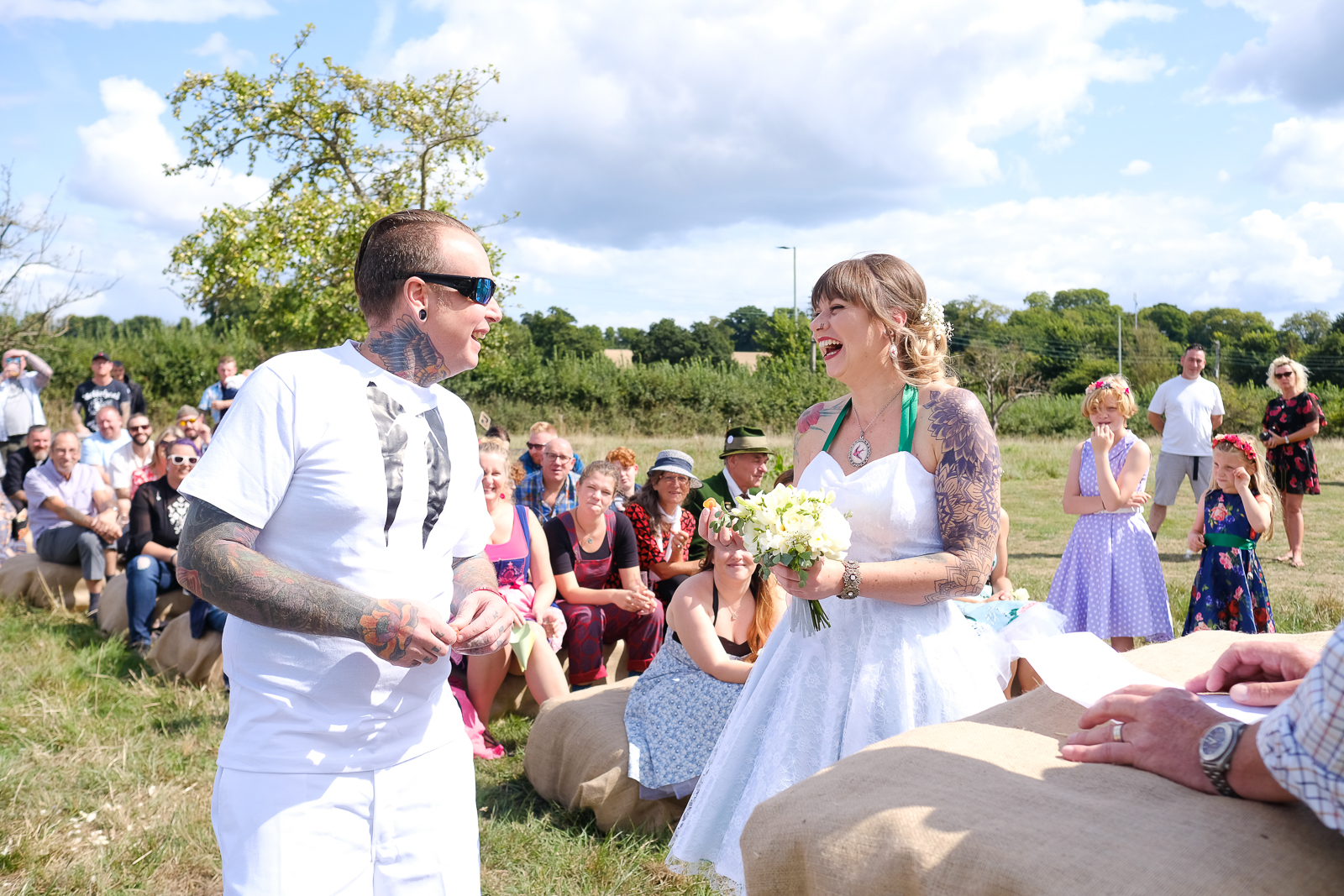 Bride and Groom laughing during their Festival Wedding ceremony in a field in Exmouth