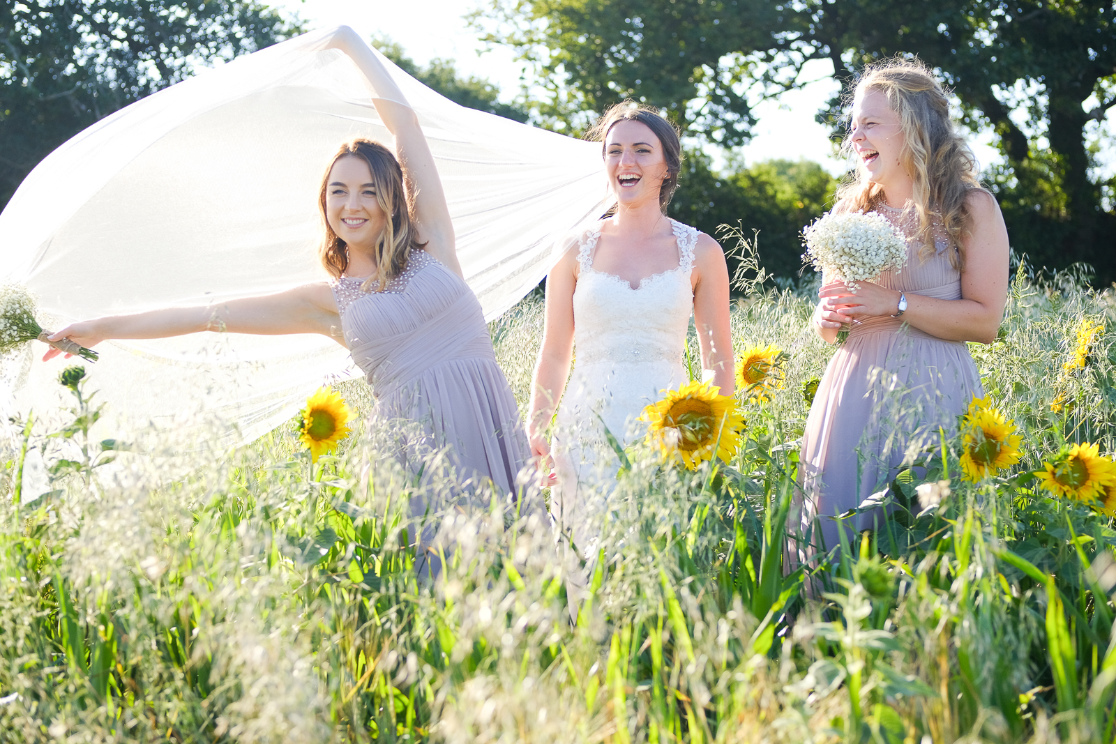 Bride and bridesmaids playing in the sunflower field at cornish wedding