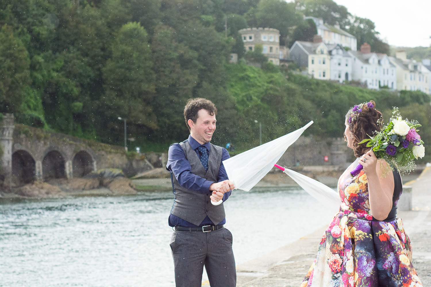 Bride and groom having a brolly fight in the rain at Looe Cornwall