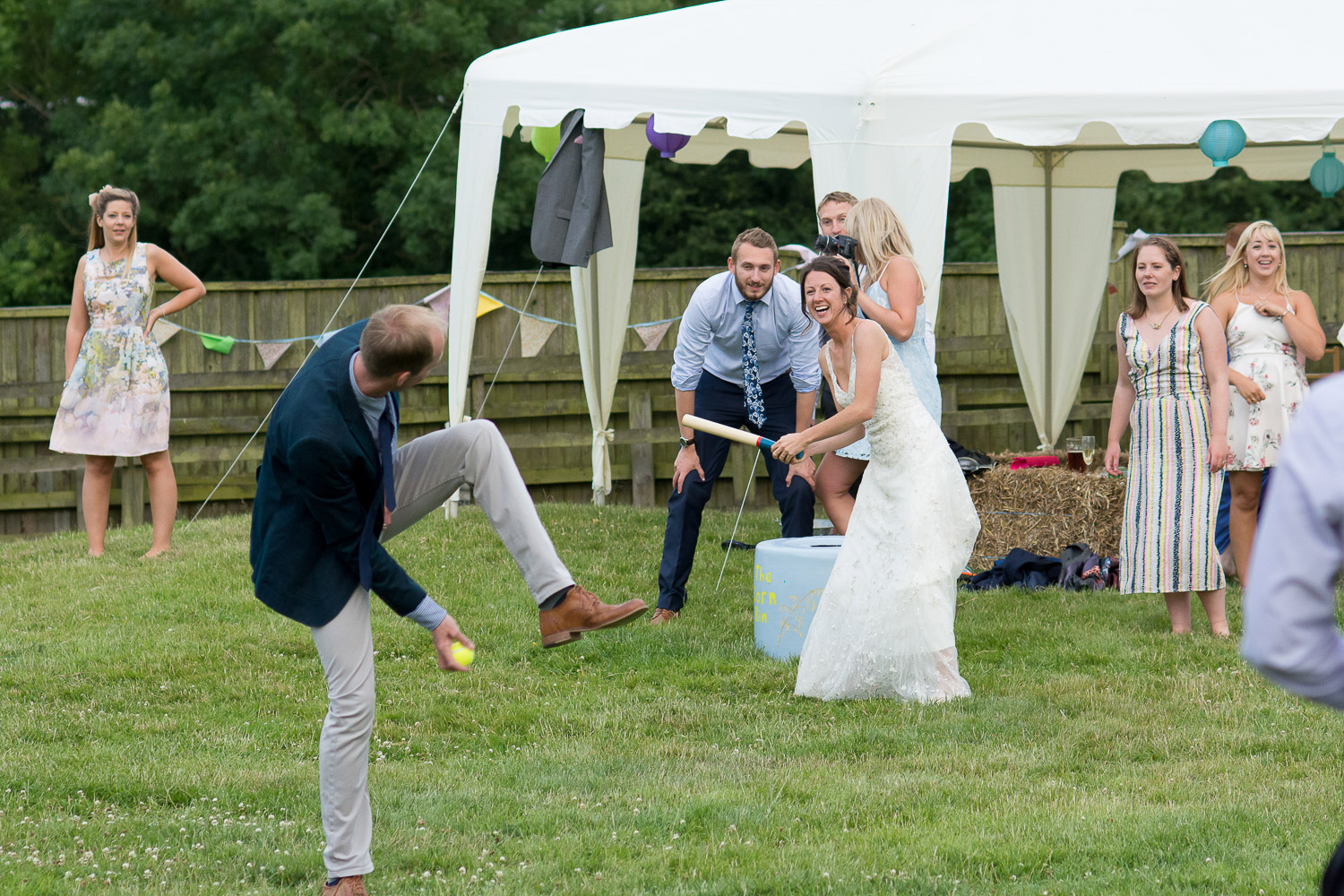 Bride playing rounders at festival style wedding