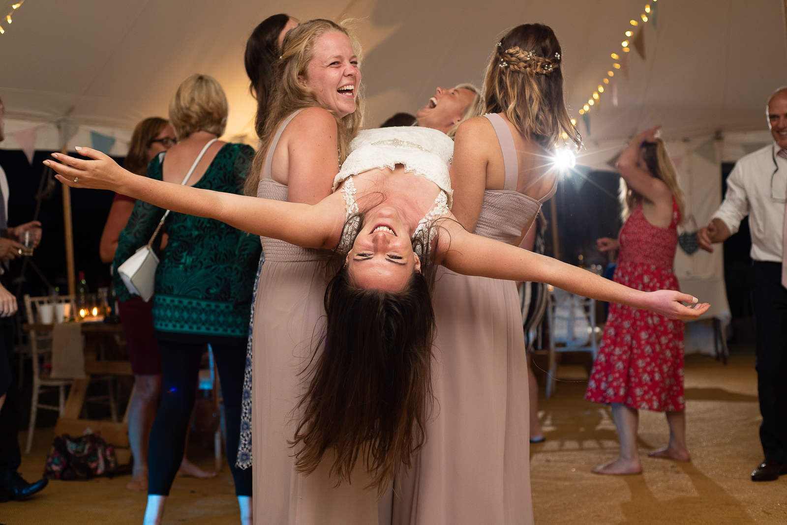 Bride being carried by friends on the dancefloor at festival style wedding in cornwall
