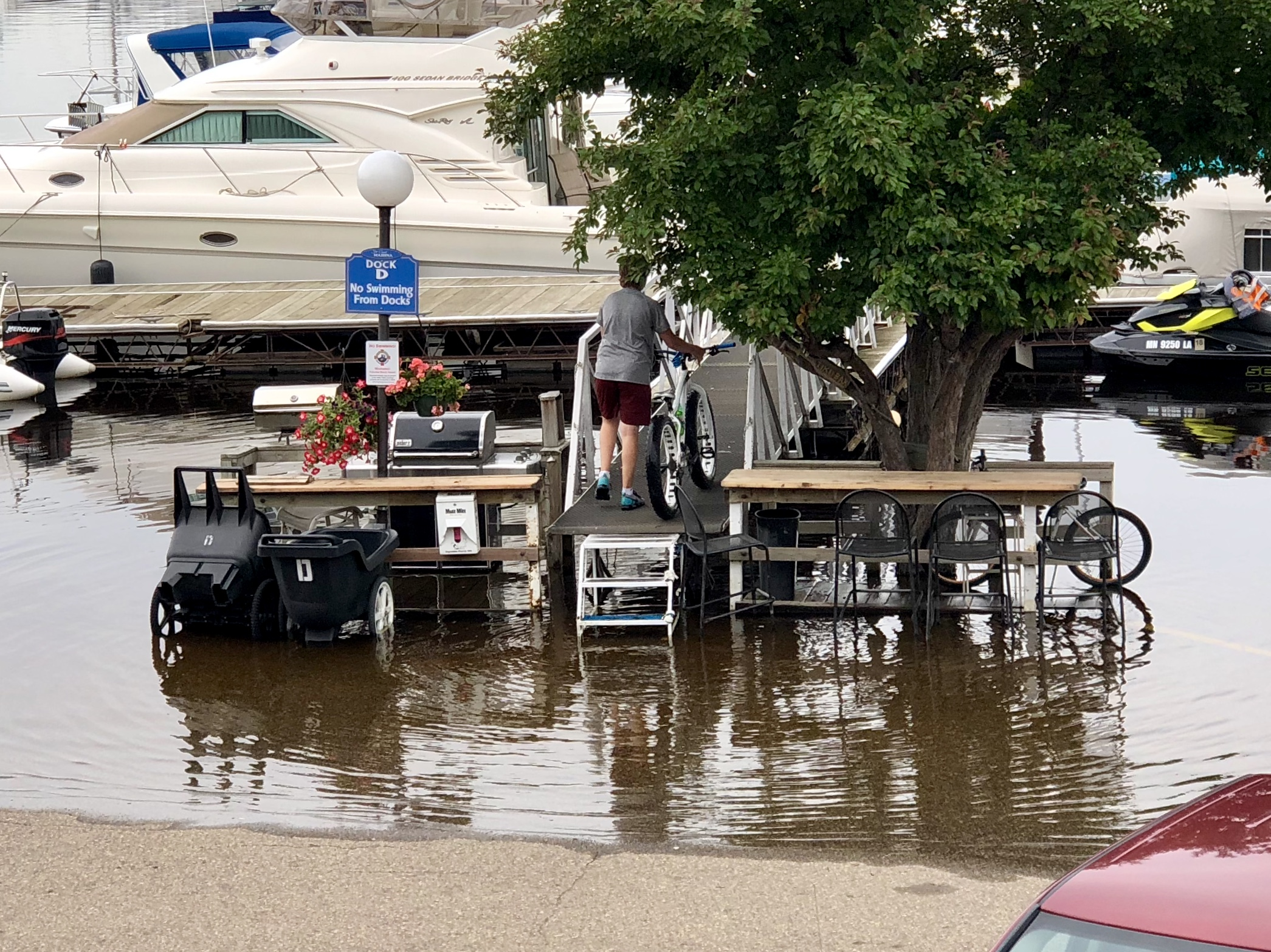 I watched this young man lift his bike up over the waterline in another section of the same parking lot, but wasn't able to get a photo until after he had waded through the water and made it up the steps.