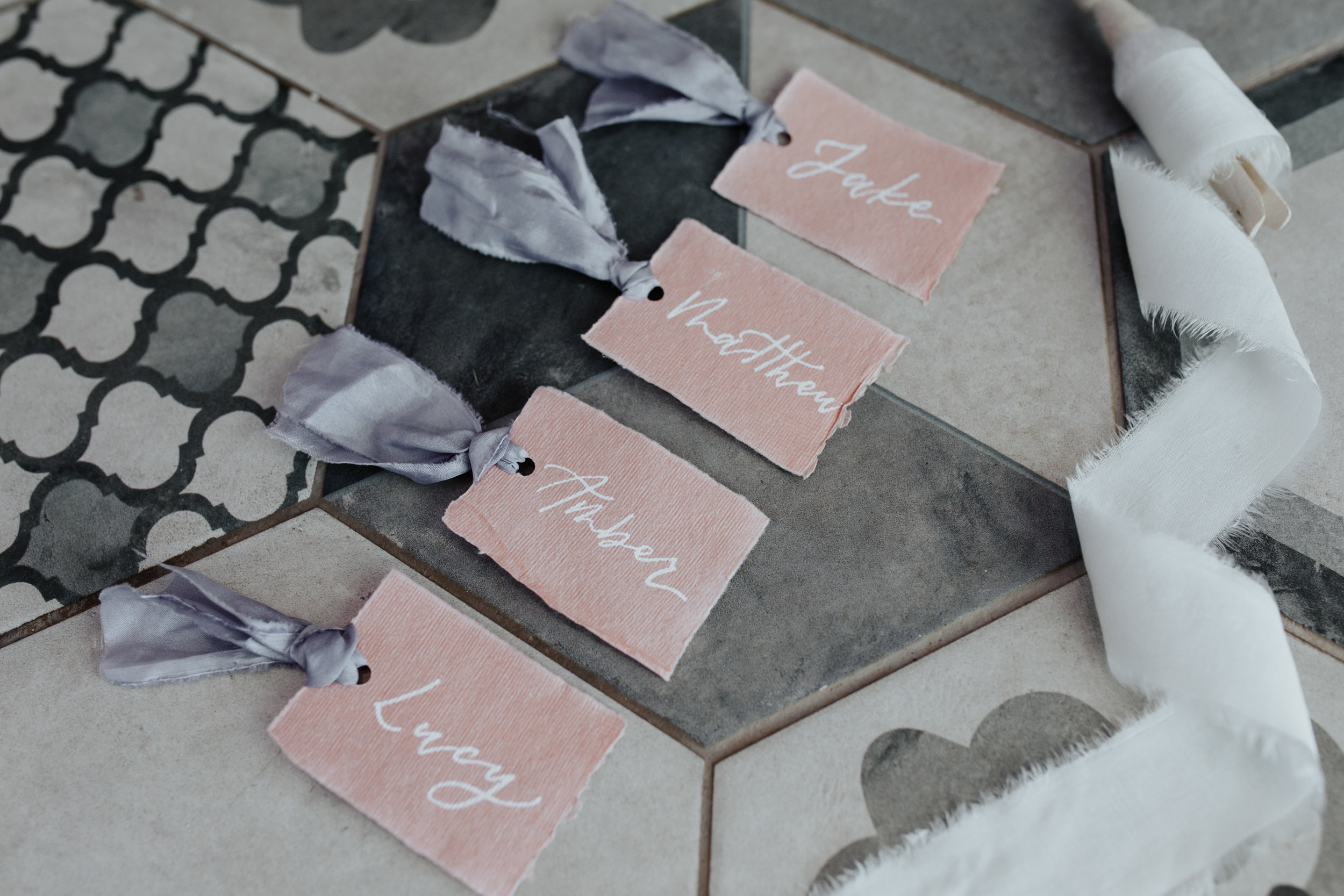 Modern calligraphy white ink wedding place cards with silk ribbon by Studio Oudizo, Cheltenham