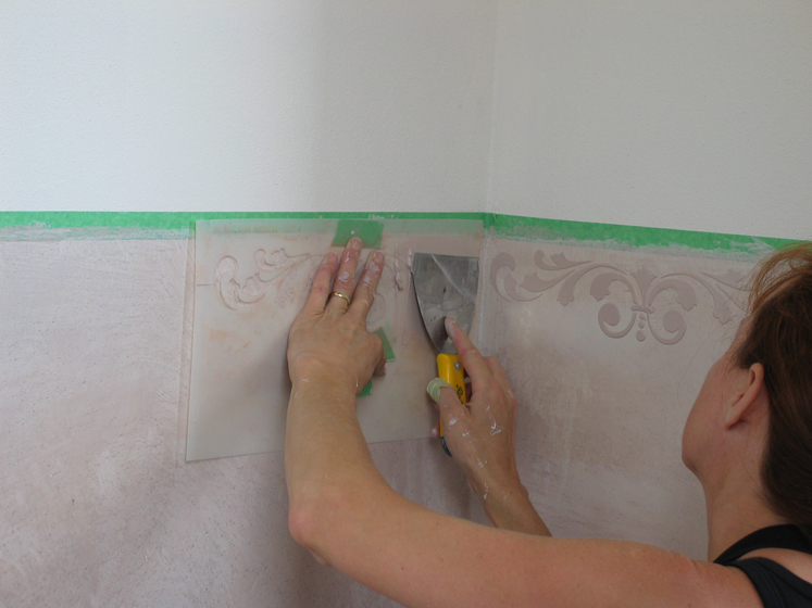 Applying an embossed stencil to the powder room dado.
