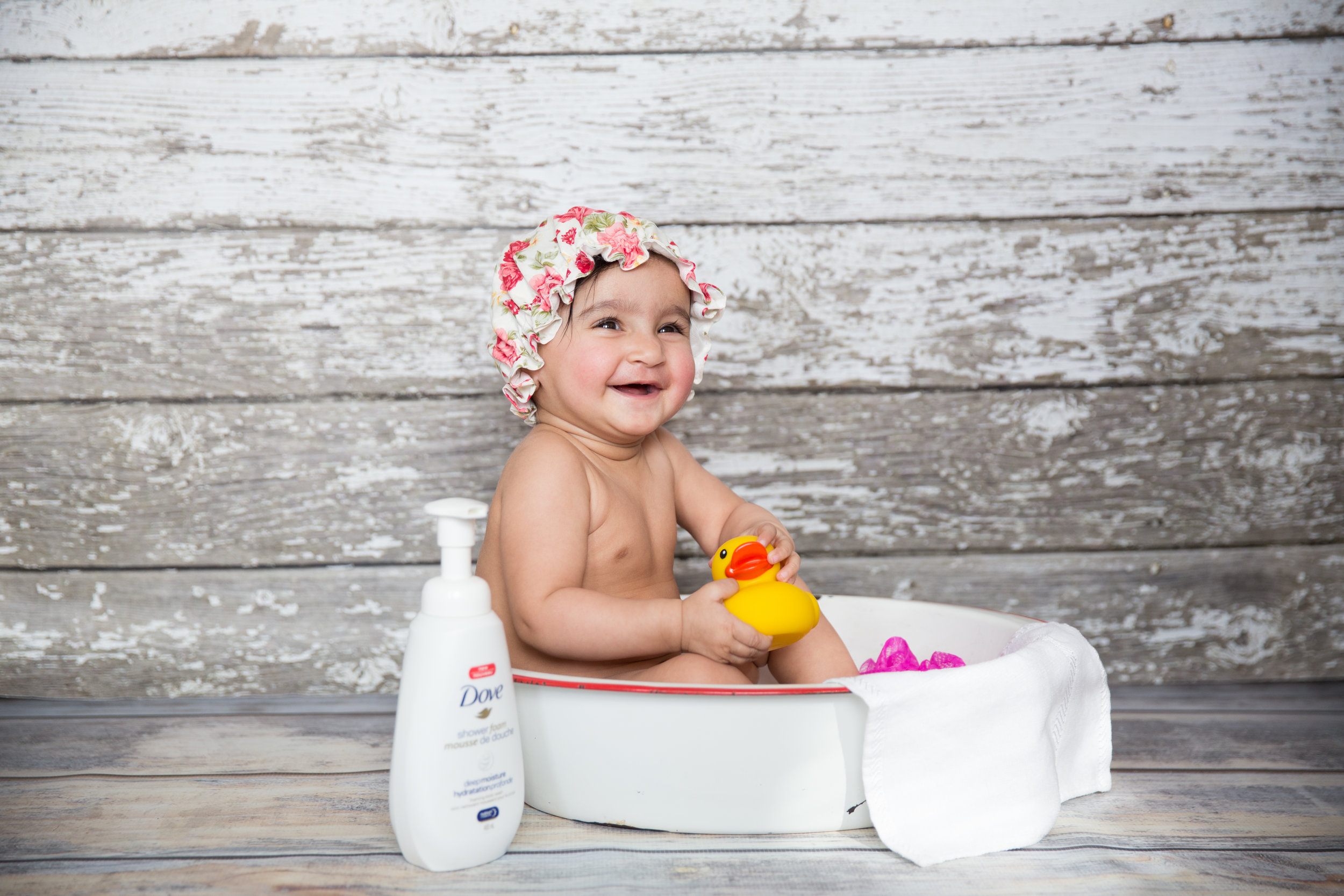 Adorable baby girl in a bathtub with a rubber duck. Calgary baby photoshoot