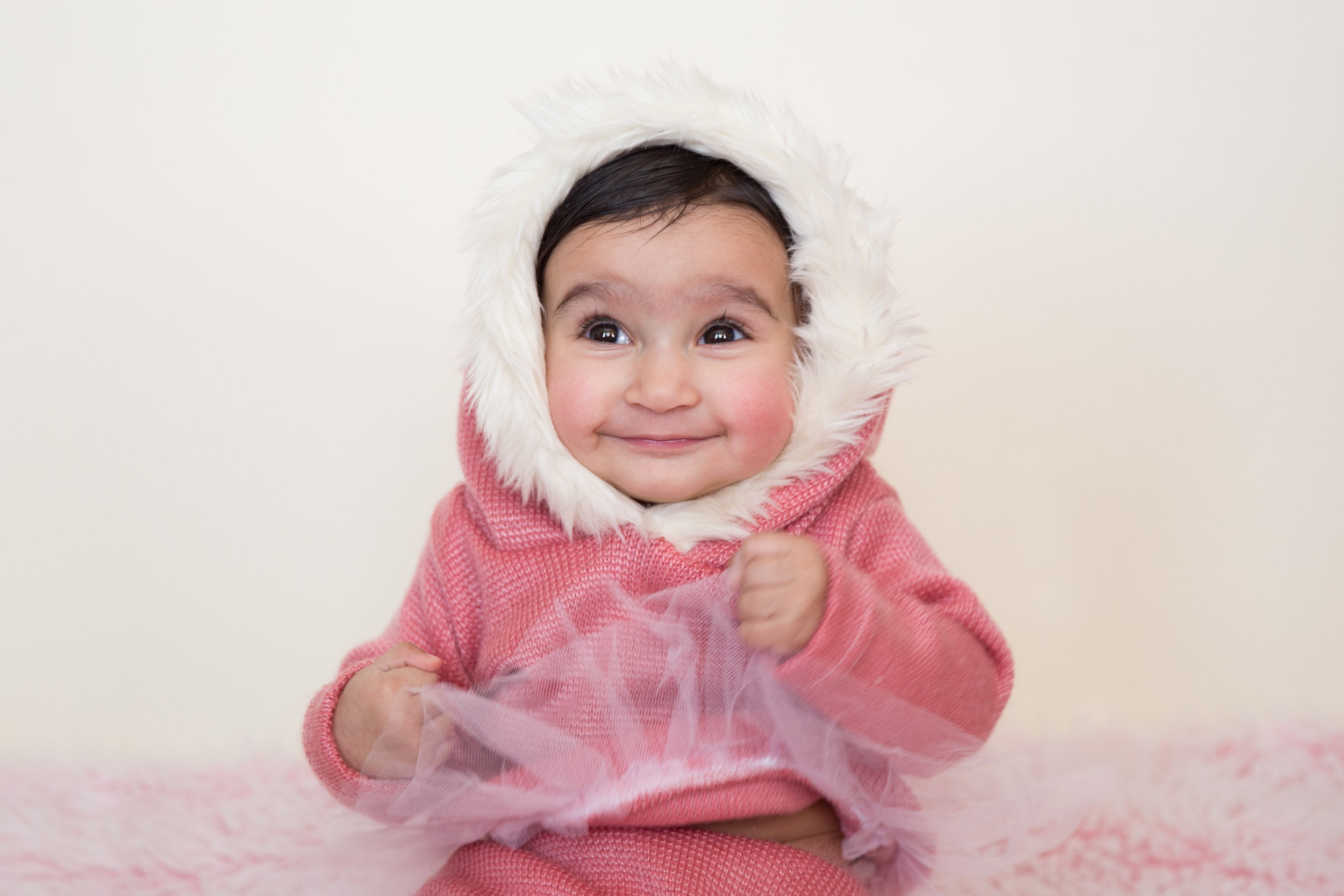 Sweet little baby girl in a pink outfit. Calgary baby photographer.