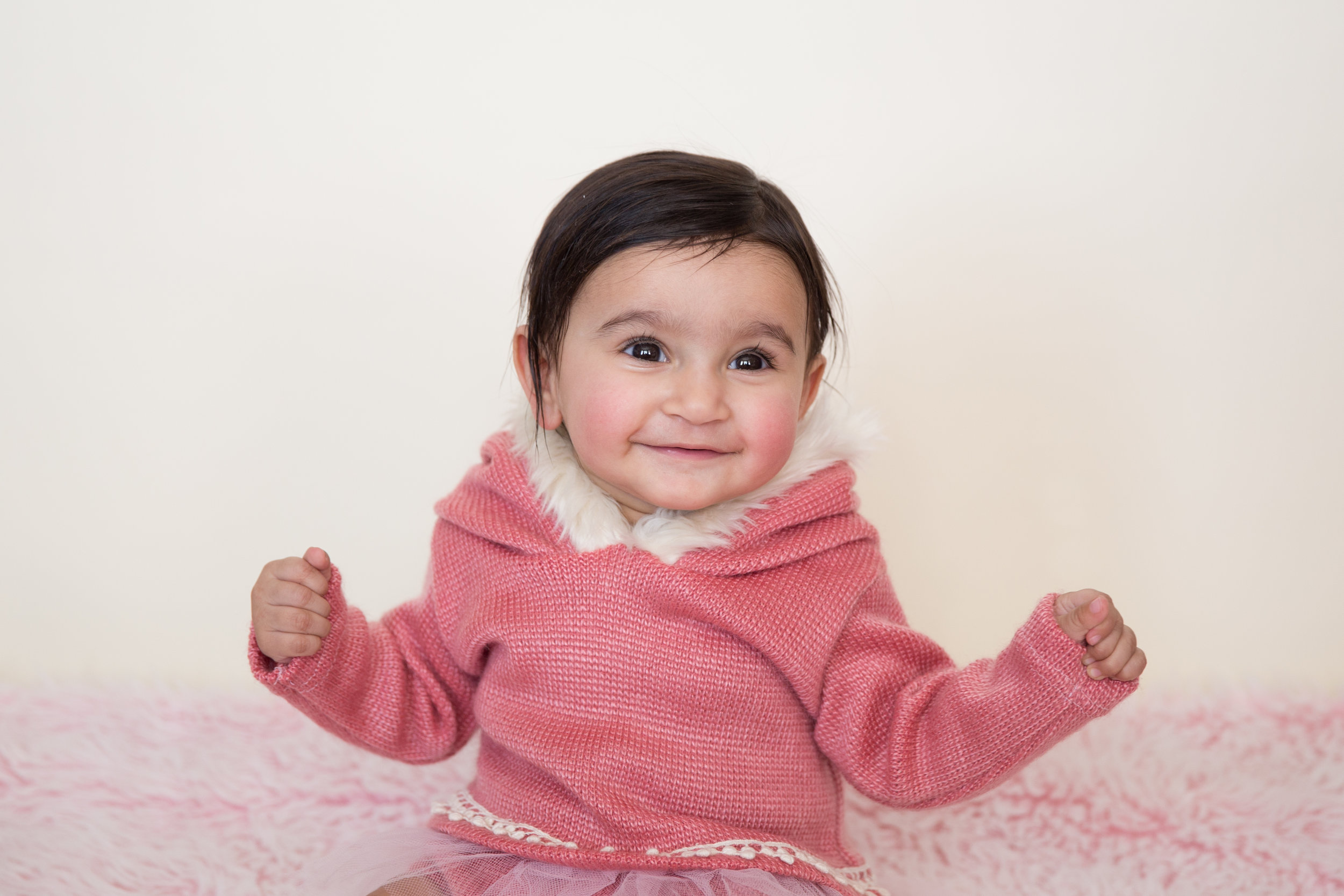 Adorable baby girl in a pink wintery outfit for a Calgary baby milestone photo session.