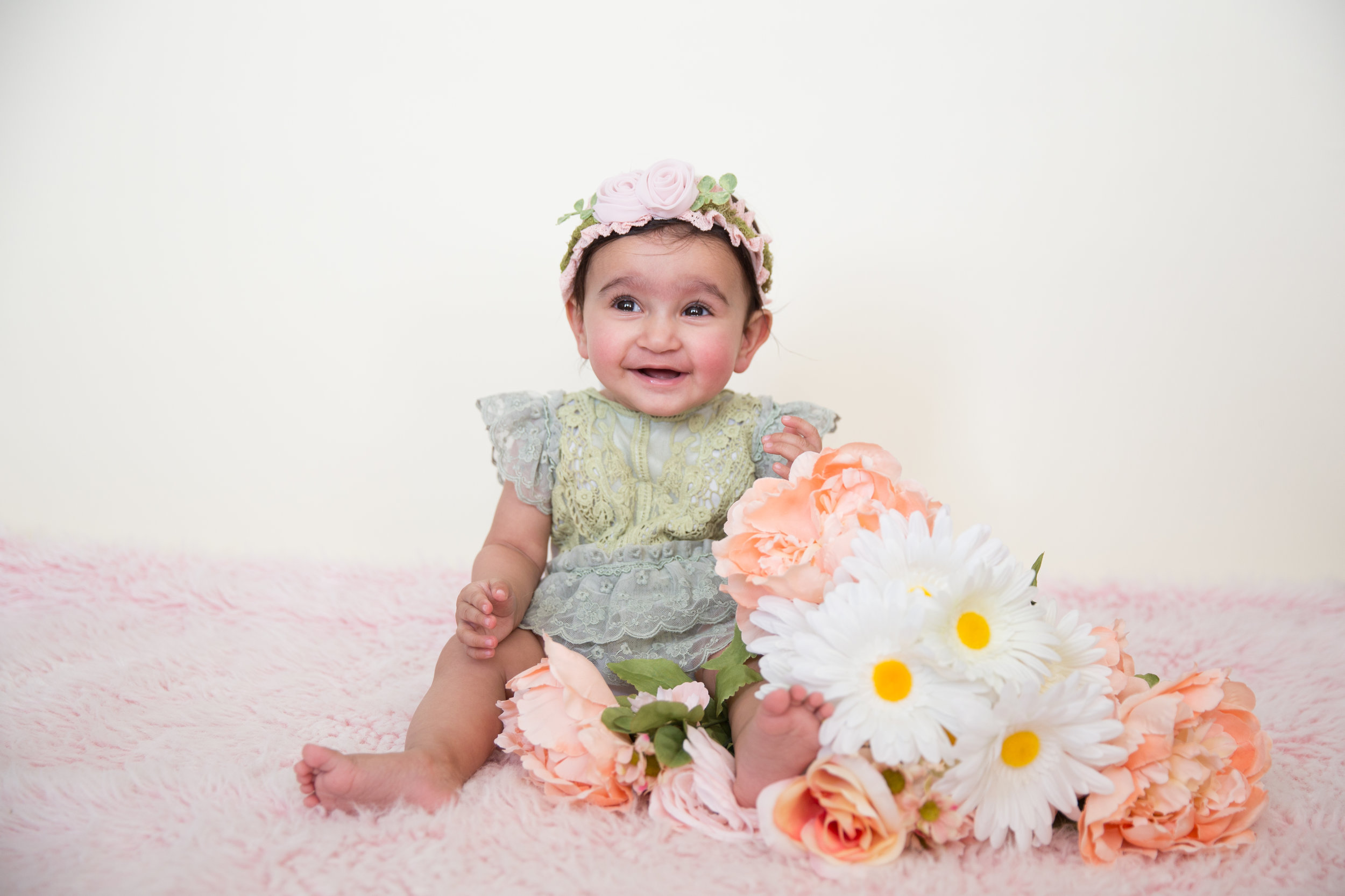 Baby girl in a cute spring outfit with flowers. Photoshoot idea. Calgary baby milestone photographer
