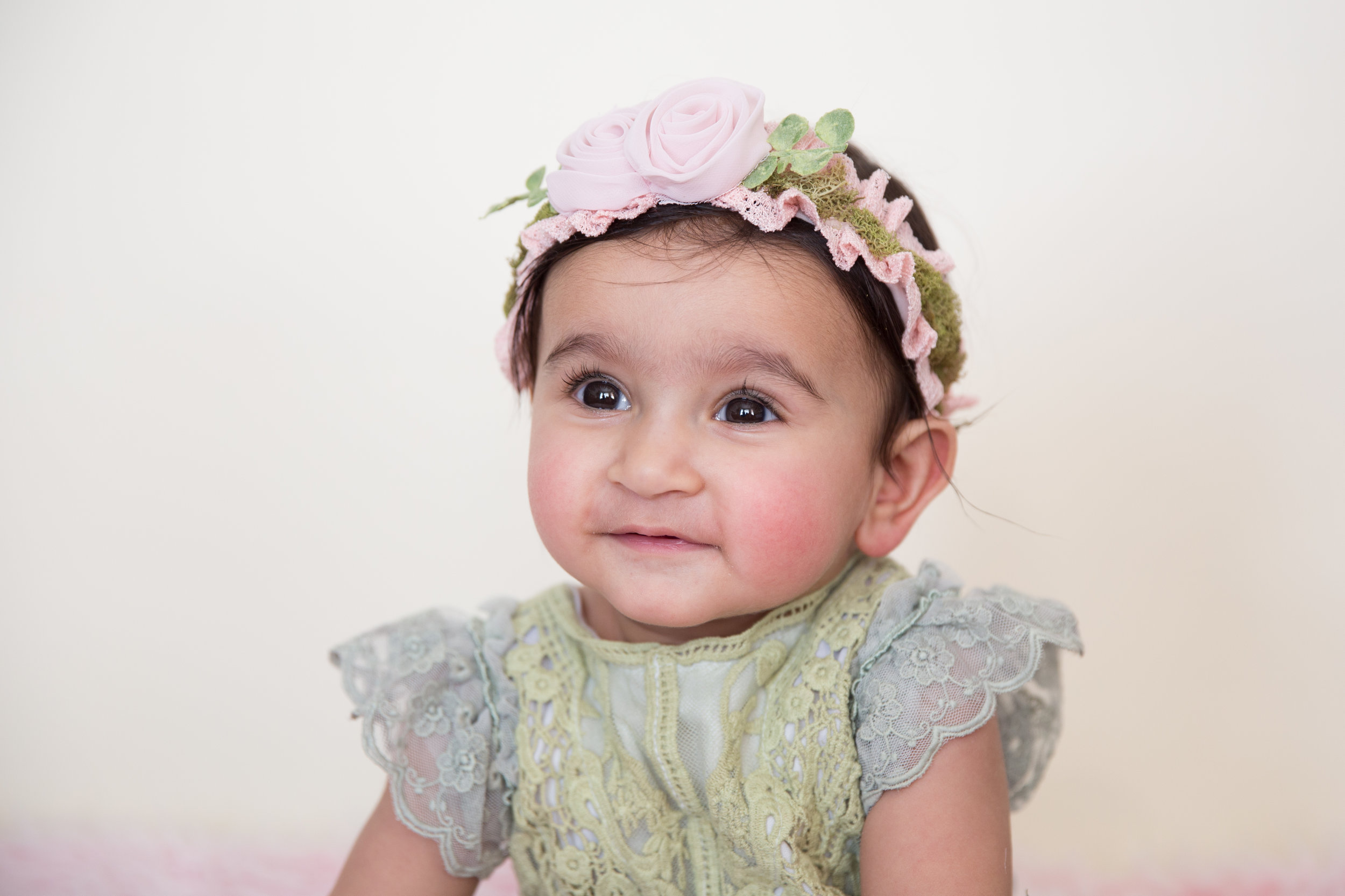Sweet little baby girl in a spring outfit for her milestone baby session with a Calgary photographer