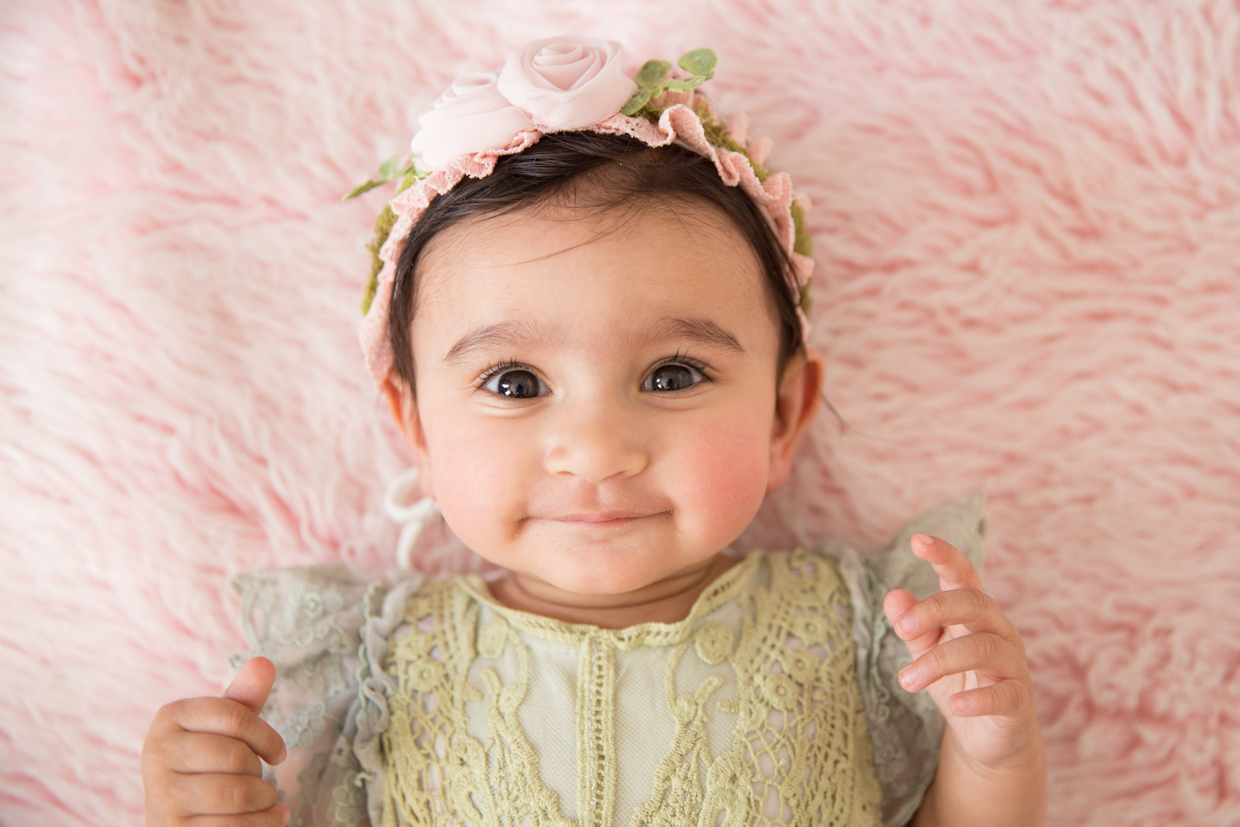 Baby girl during her baby milestone session wearing cute spring outfit and smiling for a Calgary baby photographer