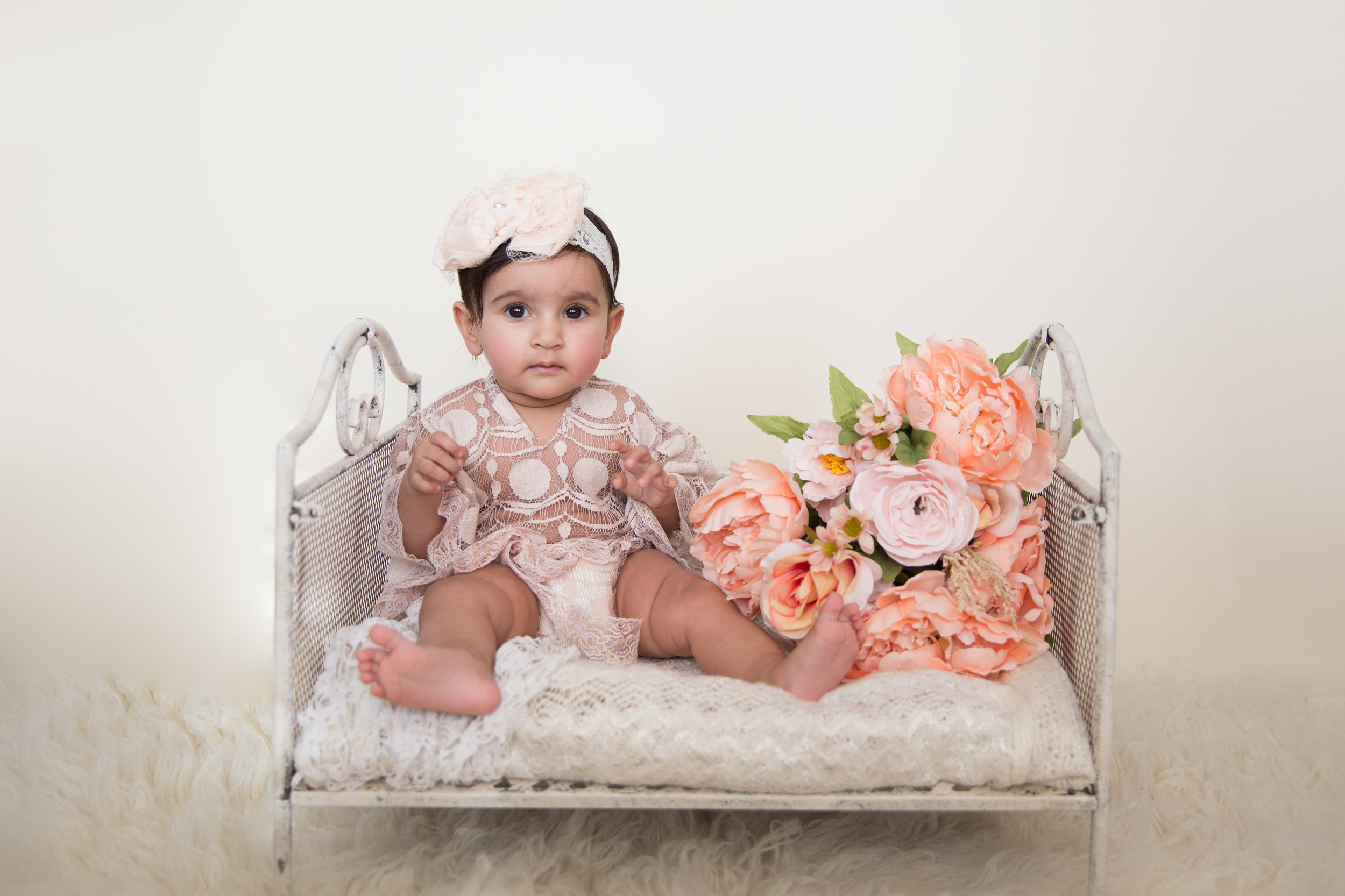 Adorable baby girl wearing lace outfit and sitting on a vintage bed surrounded by flowers. Calgary Baby Photographer