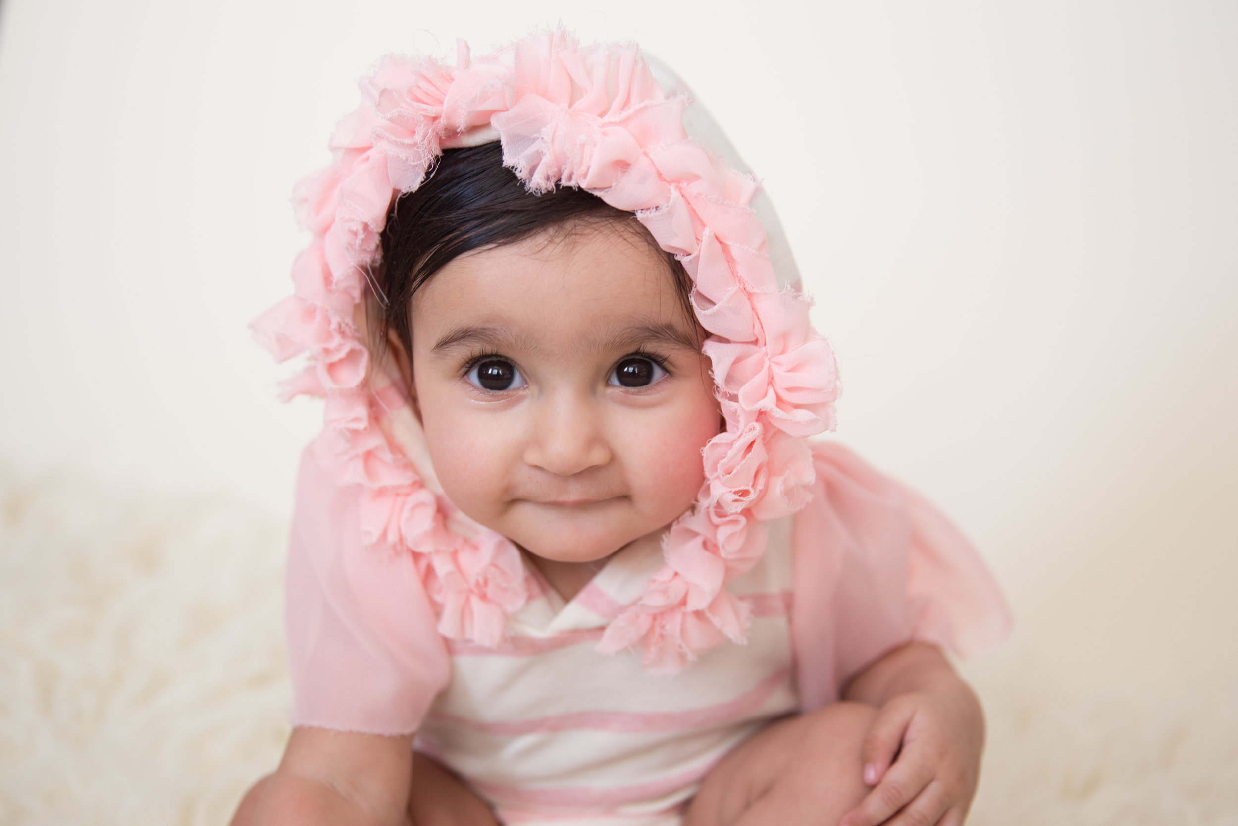 Sweet adorable baby girl rocking her Baby milestone session in a cute pink outfit with Airdrie photographer