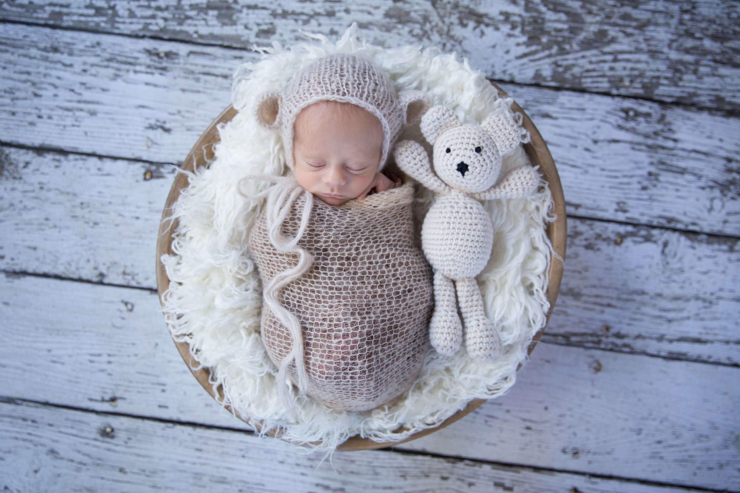 Sweet little baby boy wearing bear hat in a bowl with a little plush bear toy. Calgary Newborn Photographer.