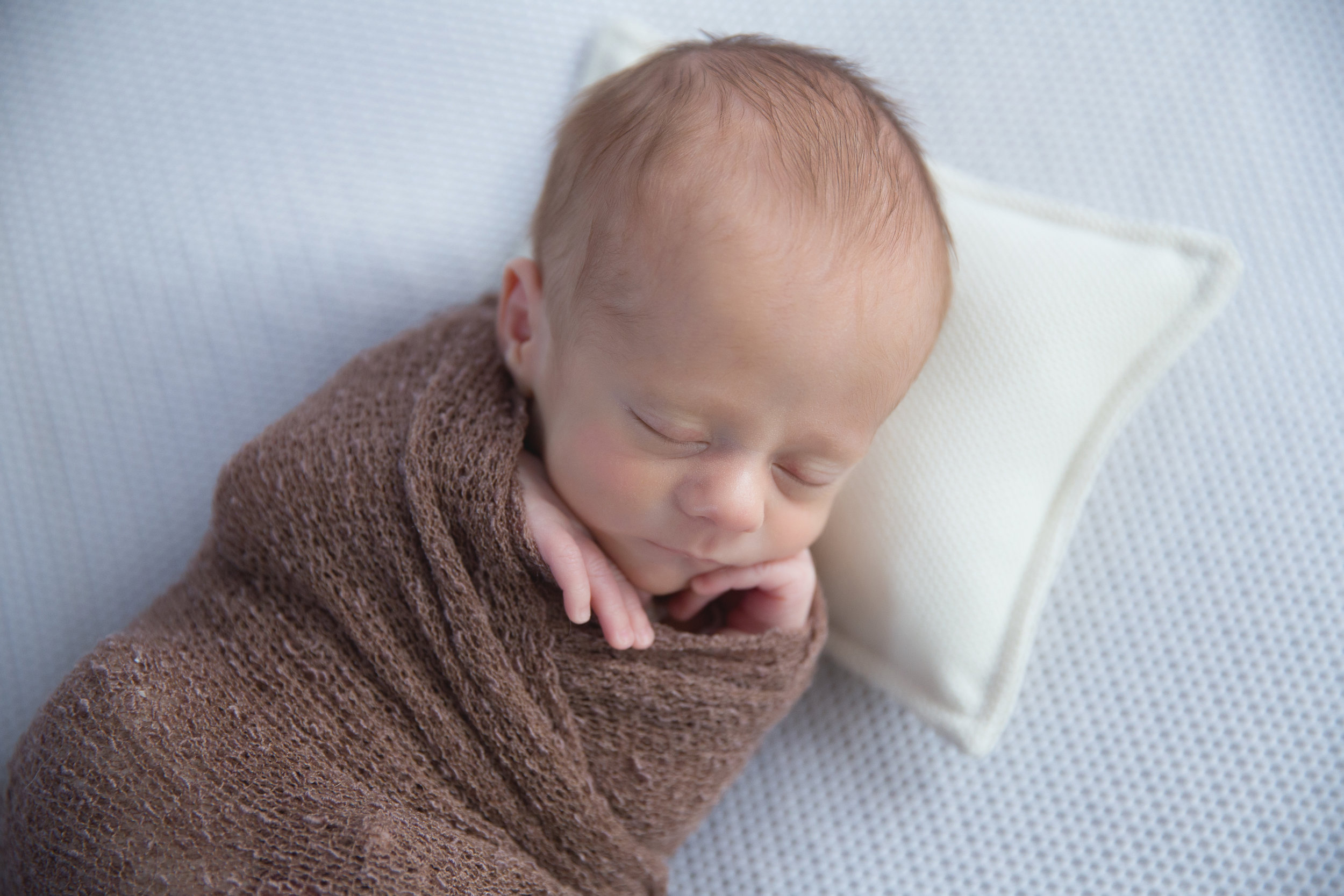 Sweet little newborn baby boy all swaddled and sleeping soundly. Newborn photographer in Calgary Alberta