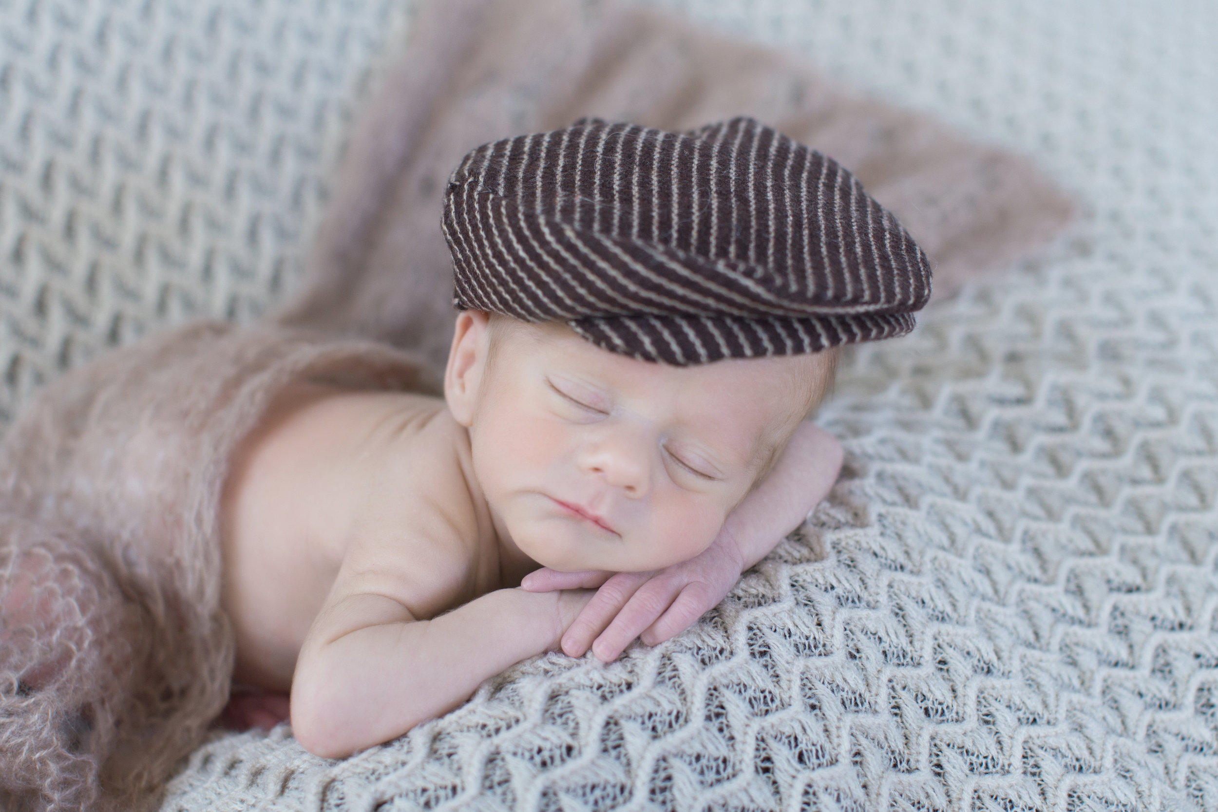 Newborn baby sleeping soundly and wearing a cute hat. Captured by Milashka photography.