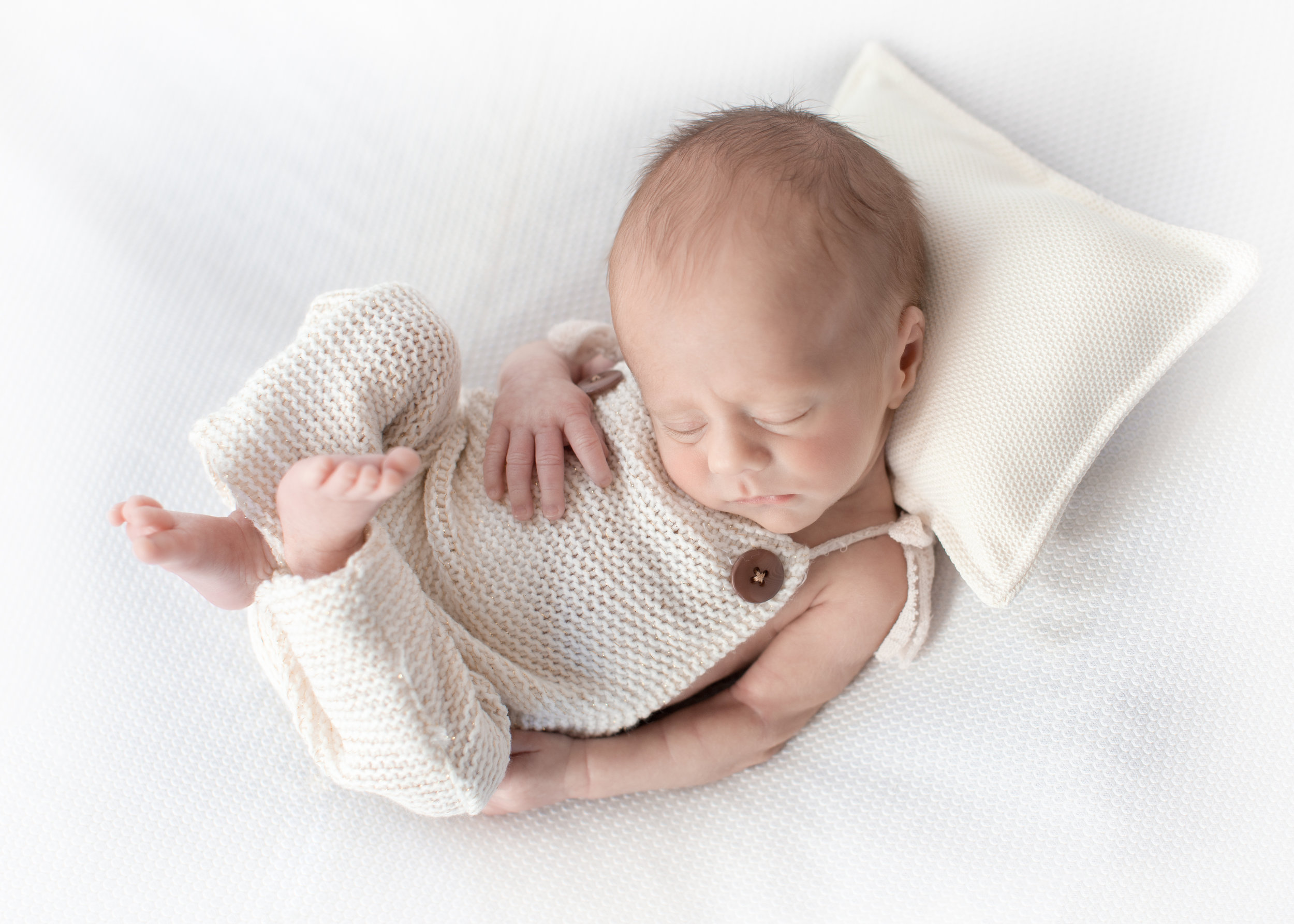 Sweet little newborn baby boy sleeping soundly on a pillow wearing a cute little outfit. Calgary and Airdrie Newborn Photographer. Captured by Milashka Photography.